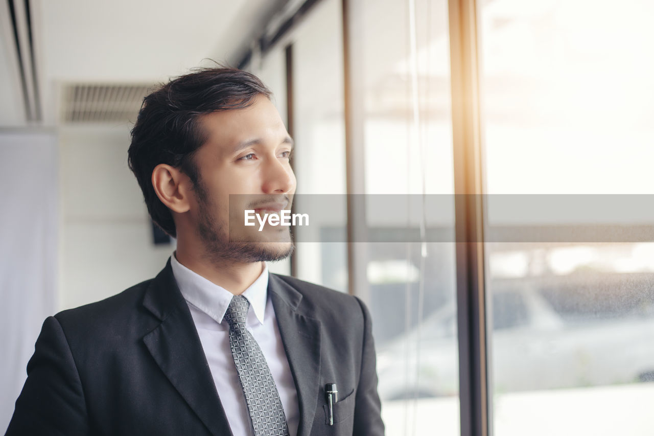 Smiling businessman looking though window in office