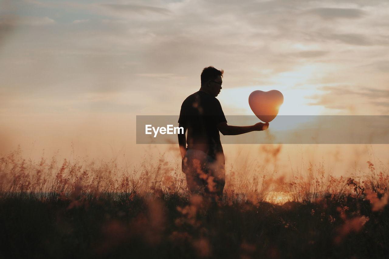 Full Length Of Man Holding Balloon On Field At Sunset