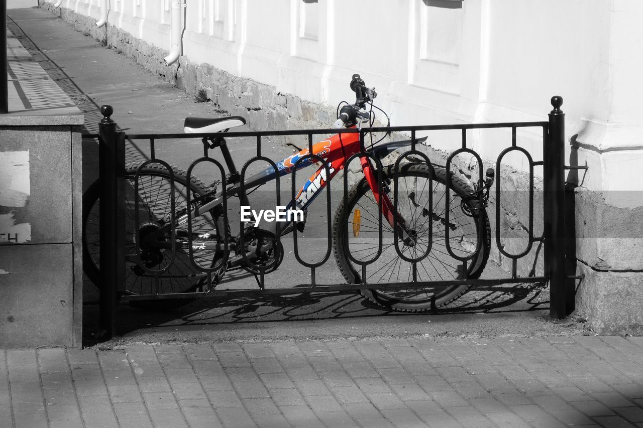 bicycle, architecture, built structure, building exterior, transportation, land vehicle, mode of transportation, city, day, wall - building feature, building, stationary, footpath, outdoors, street, no people, lifestyles, sidewalk, parking, paving stone, garage