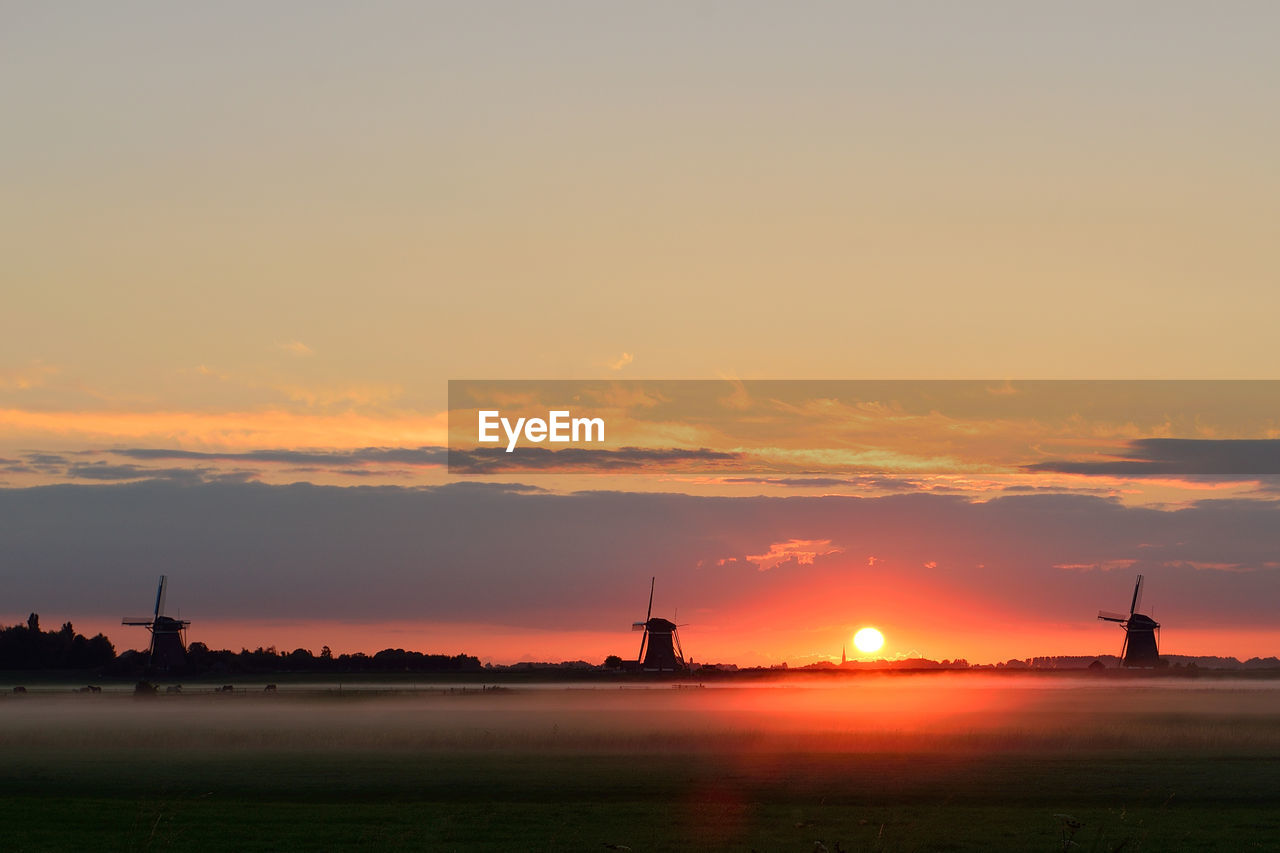 sunset, sky, orange color, silhouette, cloud - sky, no people, nature, built structure, windmill, outdoors, beauty in nature, architecture, wind power, travel destinations, building exterior, traditional windmill, alternative energy, wind turbine, water, scenics, nautical vessel, industrial windmill, day