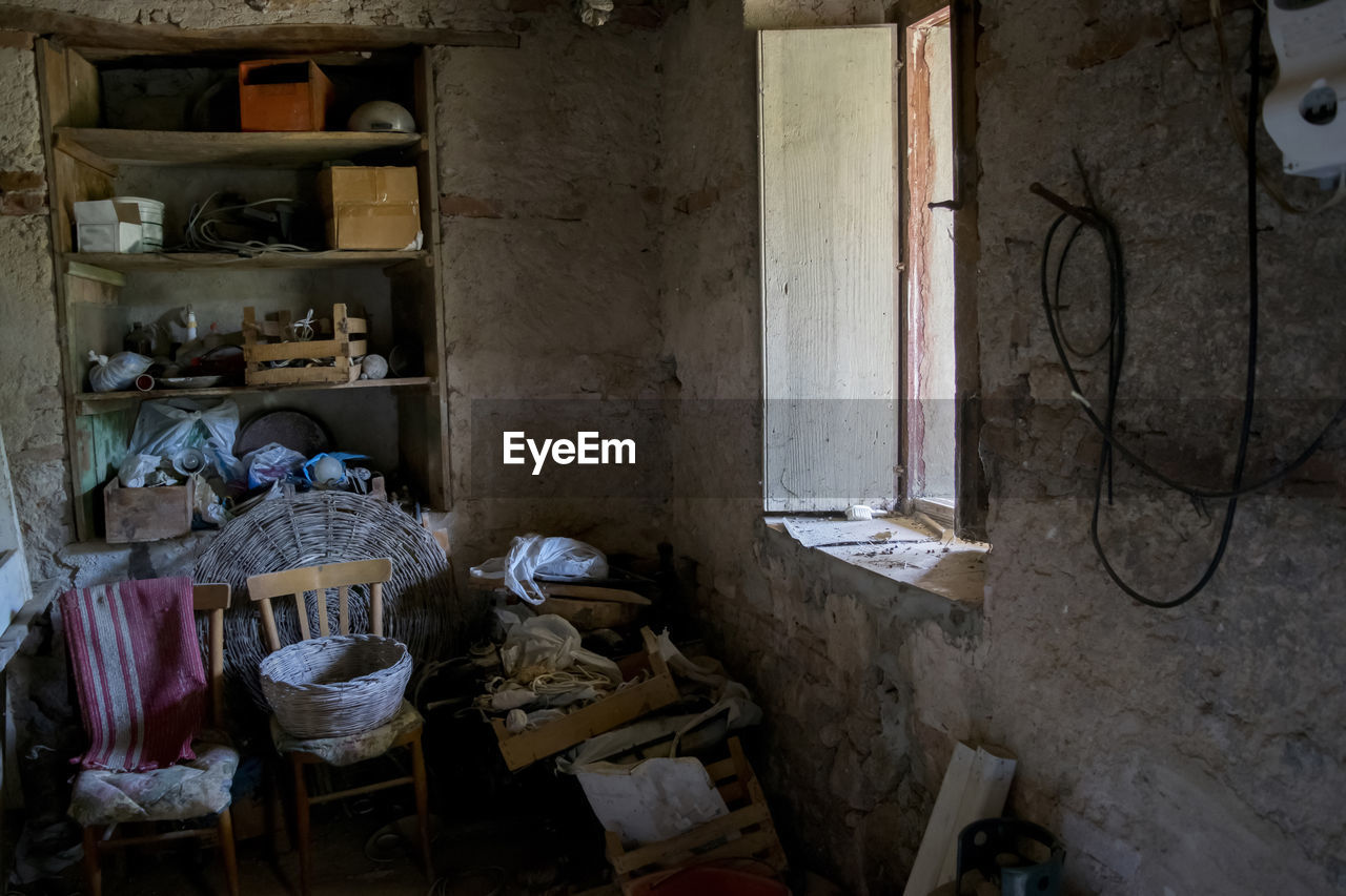 indoors, abandoned, messy, no people, large group of objects, architecture, domestic room, old, building, dirt, obsolete, decline, deterioration, dirty, furniture, bad condition, day, shelf, container, built structure