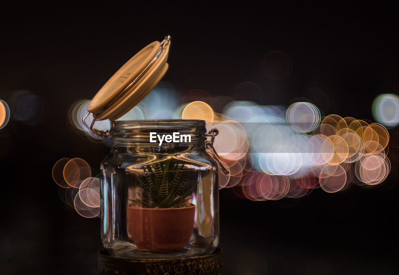 Close-up of houseplant in jar on table against illuminated light at night