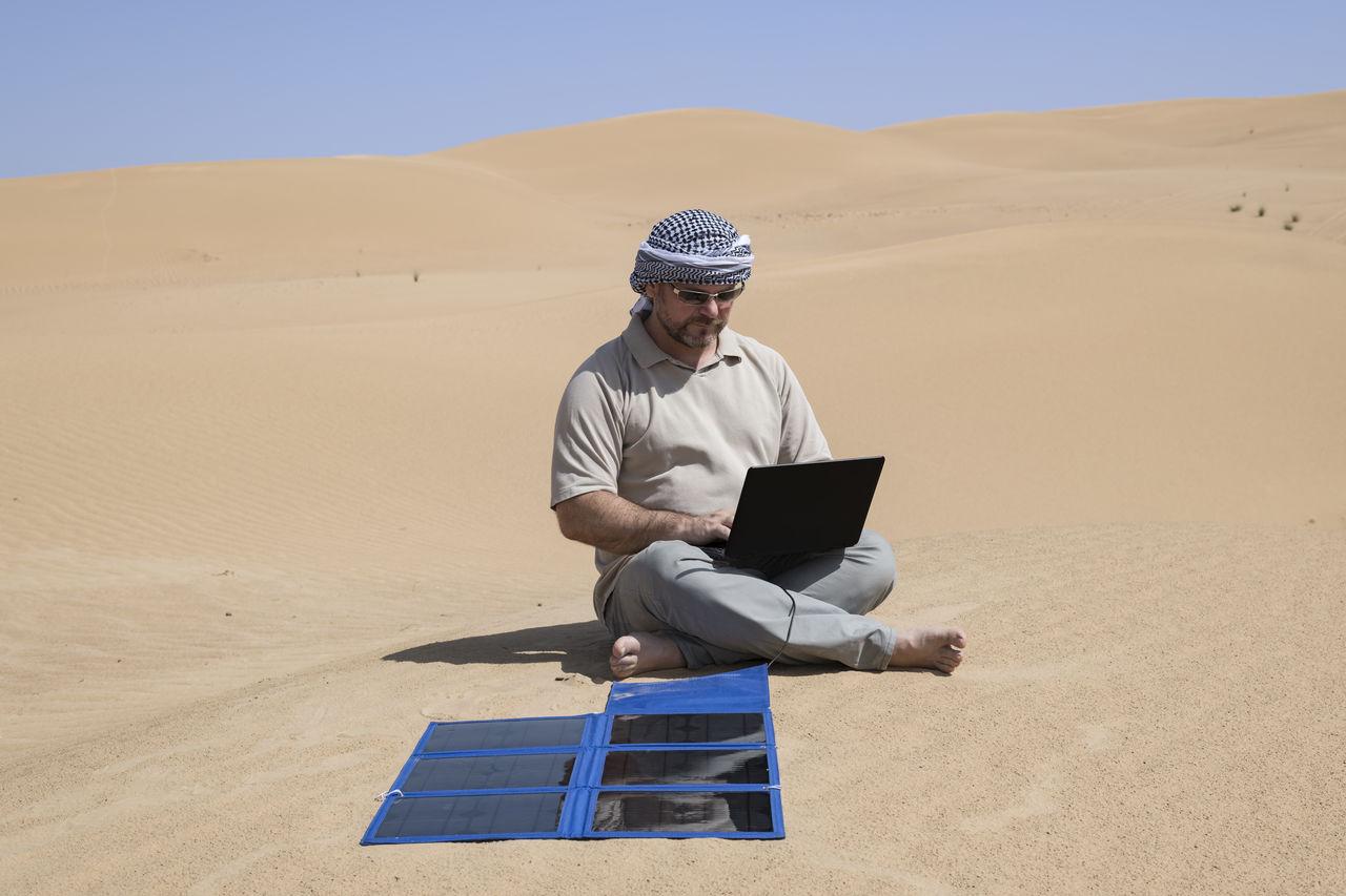 Full Length Of Man Using Laptop At Desert On Sunny Day