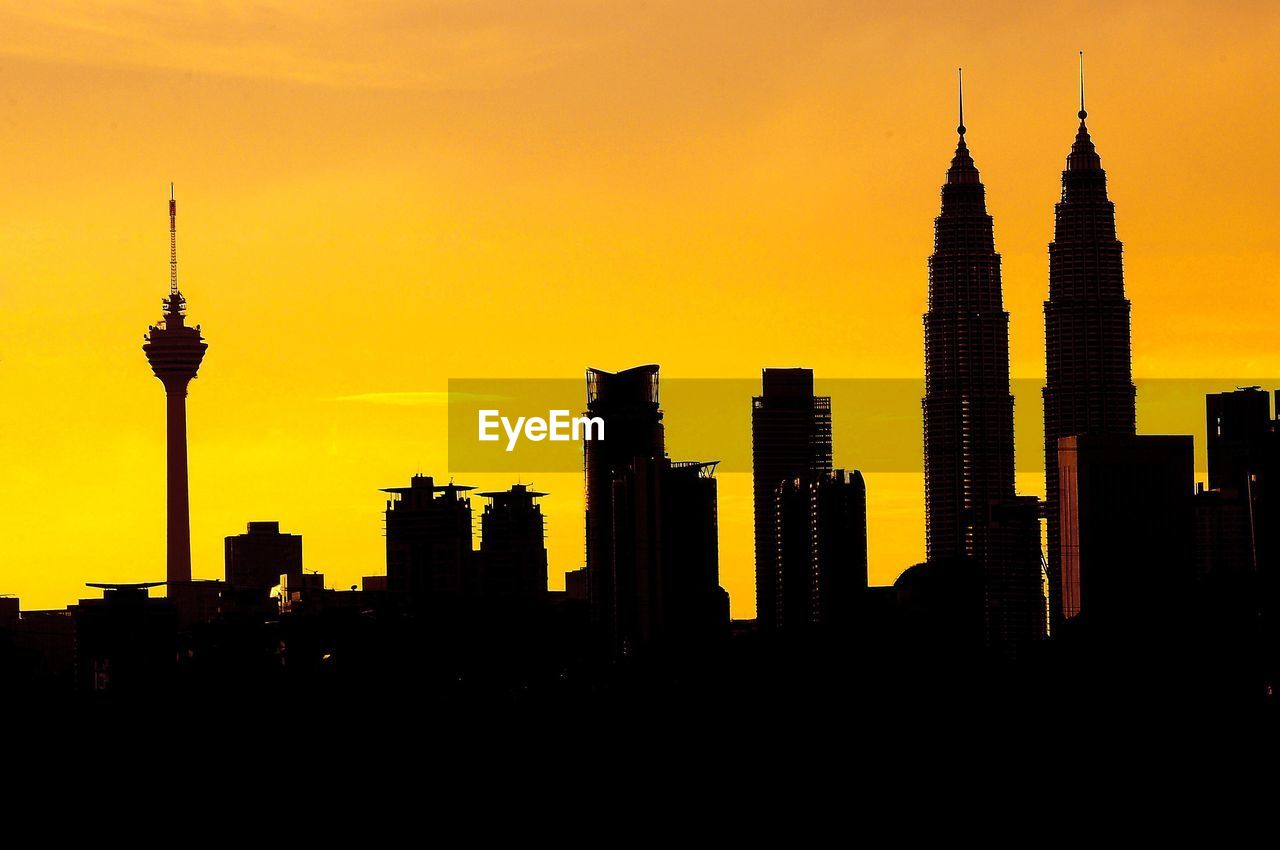 SILHOUETTE OF SKYSCRAPERS AGAINST SUNSET SKY