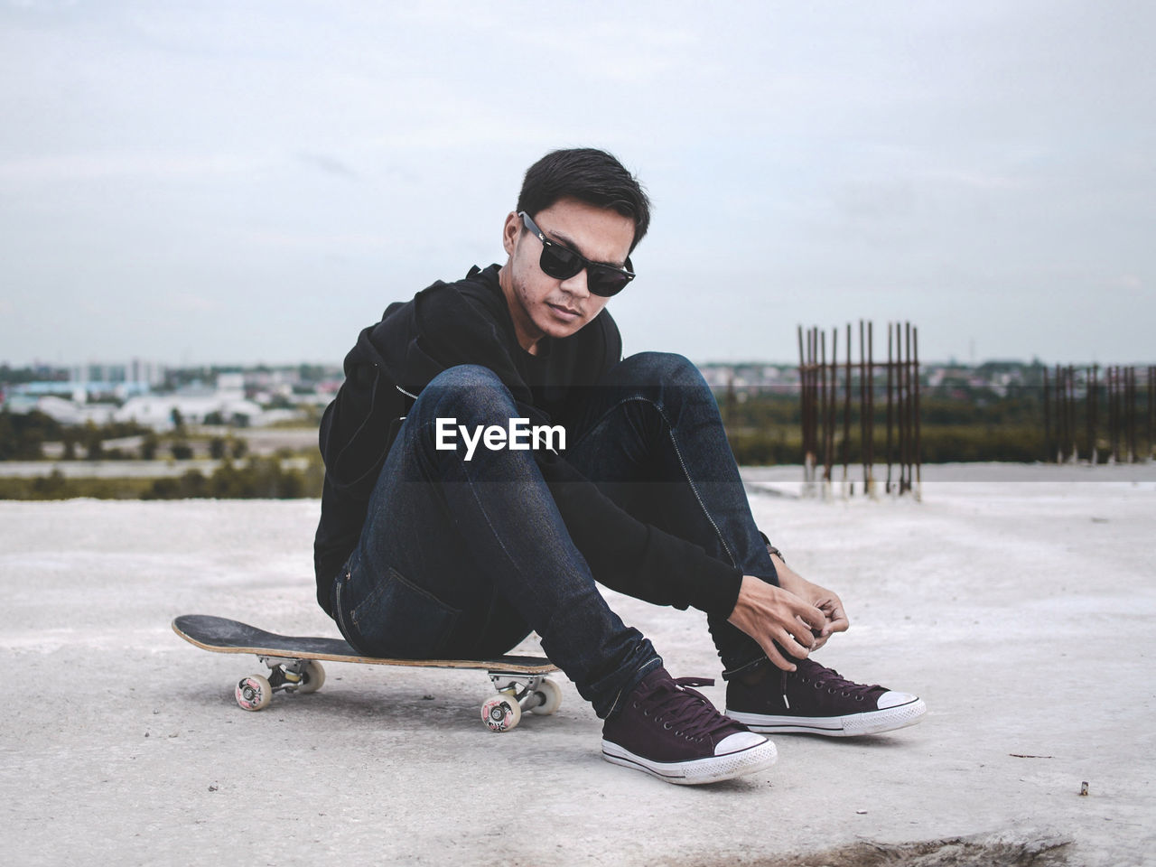 Portrait Of Man Tying Shoelace While Sitting On Skateboard At Incomplete Building