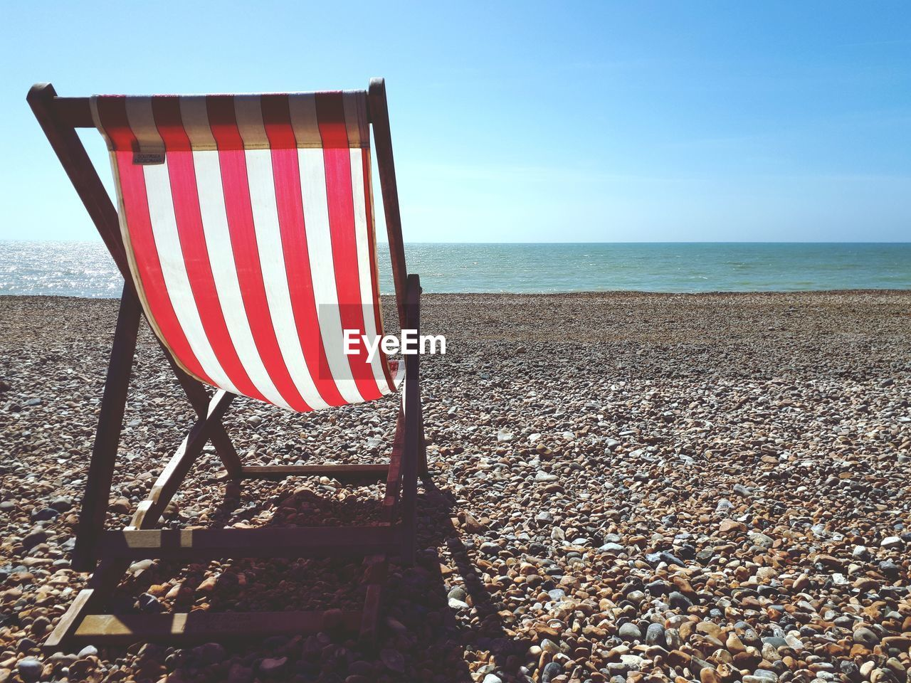 Deck chair on shore at beach during sunny day