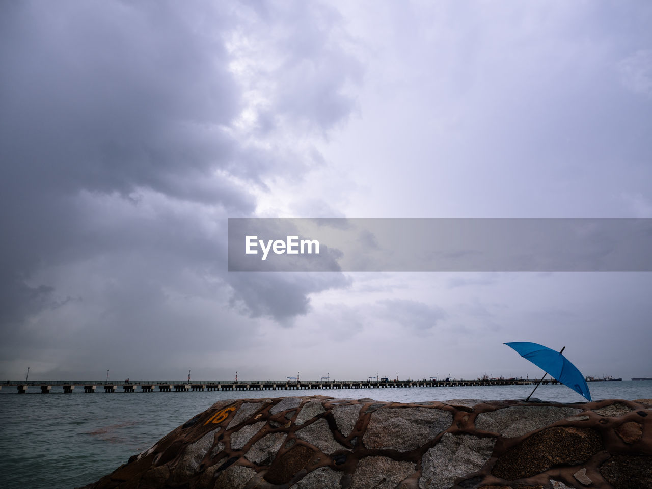 cloud - sky, sky, water, sea, nature, beauty in nature, scenics - nature, beach, land, tranquility, day, tranquil scene, protection, solid, no people, rock, outdoors, overcast, horizon over water, groyne, ominous
