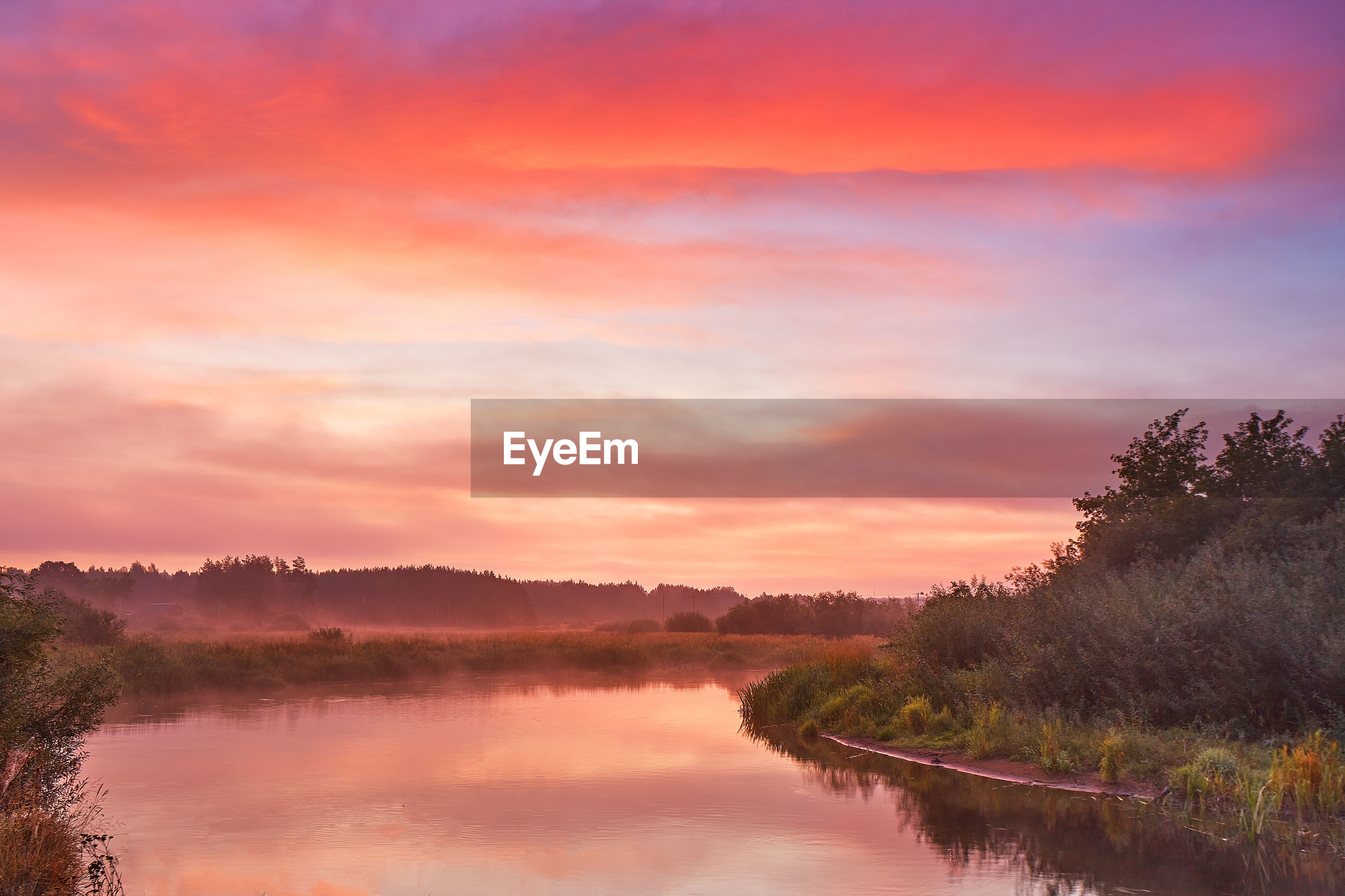 SCENIC VIEW OF LAKE BY TREES AGAINST ORANGE SKY