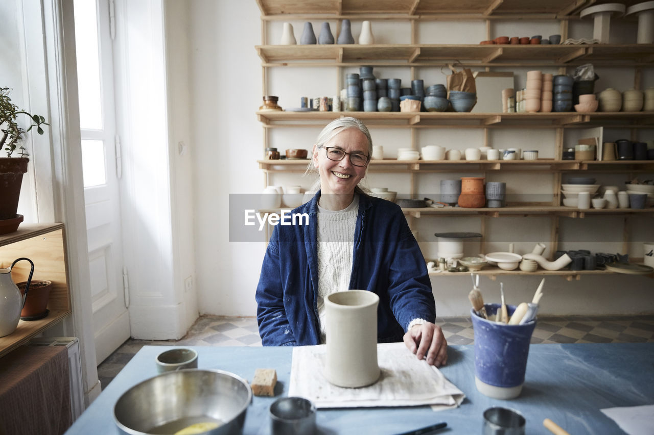PORTRAIT OF SMILING WOMAN WITH COFFEE STANDING IN KITCHEN