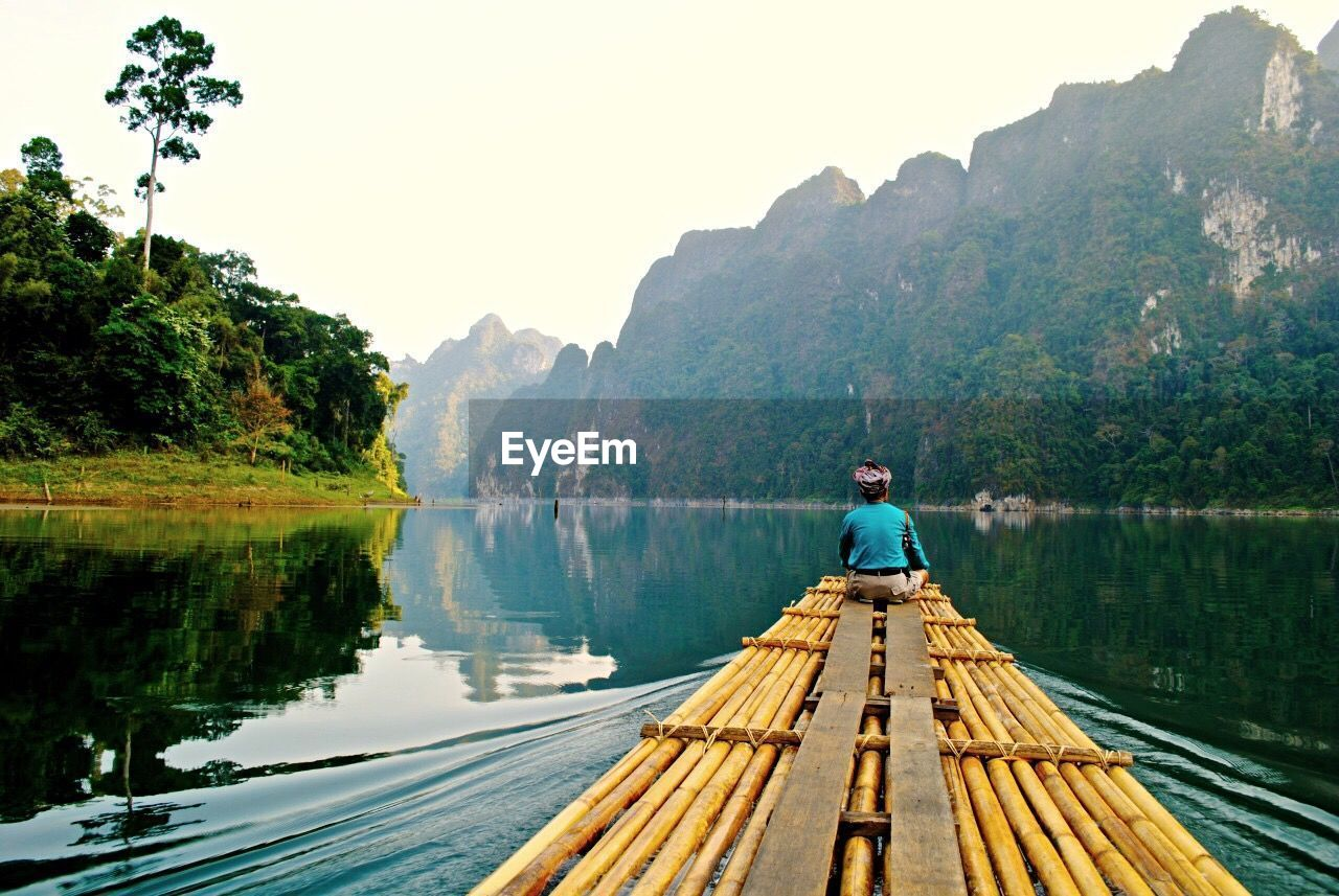 nature, beauty in nature, nautical vessel, wood - material, water, full length, outdoors, day, one person, real people, tree, lake, tranquil scene, transportation, tranquility, wooden raft, mature adult, leisure activity, standing, oar, men, scenics, sitting, mountain, clear sky, adult, sky, people