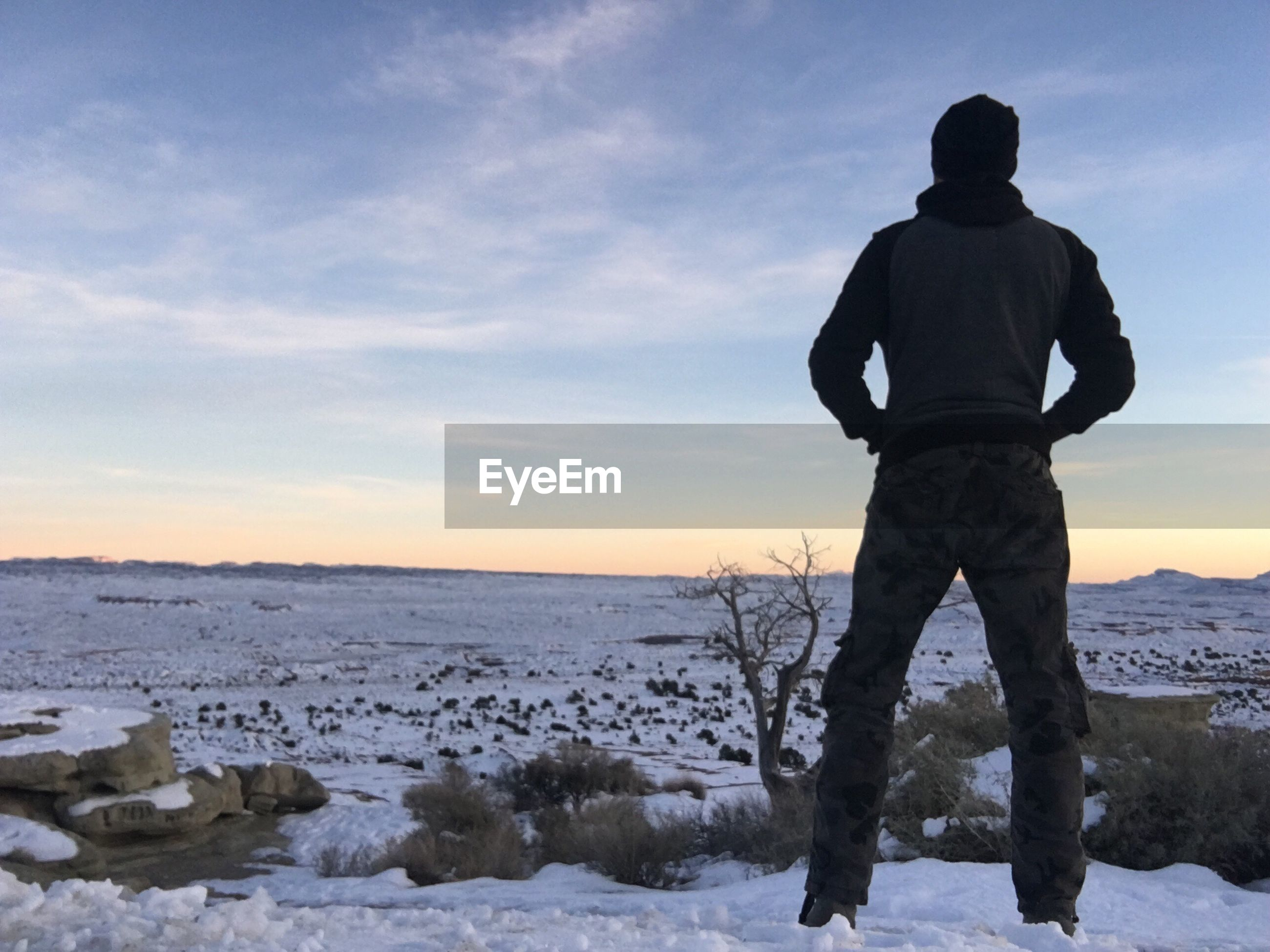 winter, cold temperature, snow, one person, one man only, standing, only men, sunset, outdoors, men, full length, sky, adult, adults only, people, beauty in nature, day