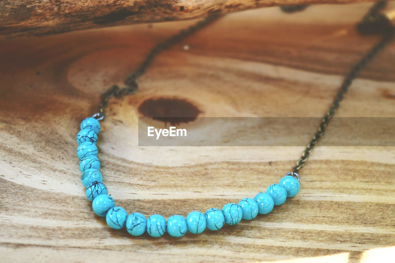High angle view of bead necklace on wooden table