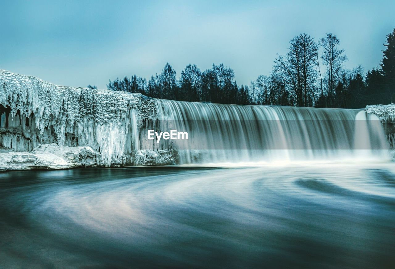 scenics - nature, water, beauty in nature, waterfall, tree, long exposure, motion, flowing water, sky, cold temperature, no people, blurred motion, nature, environment, plant, non-urban scene, winter, day, flowing, outdoors, power in nature