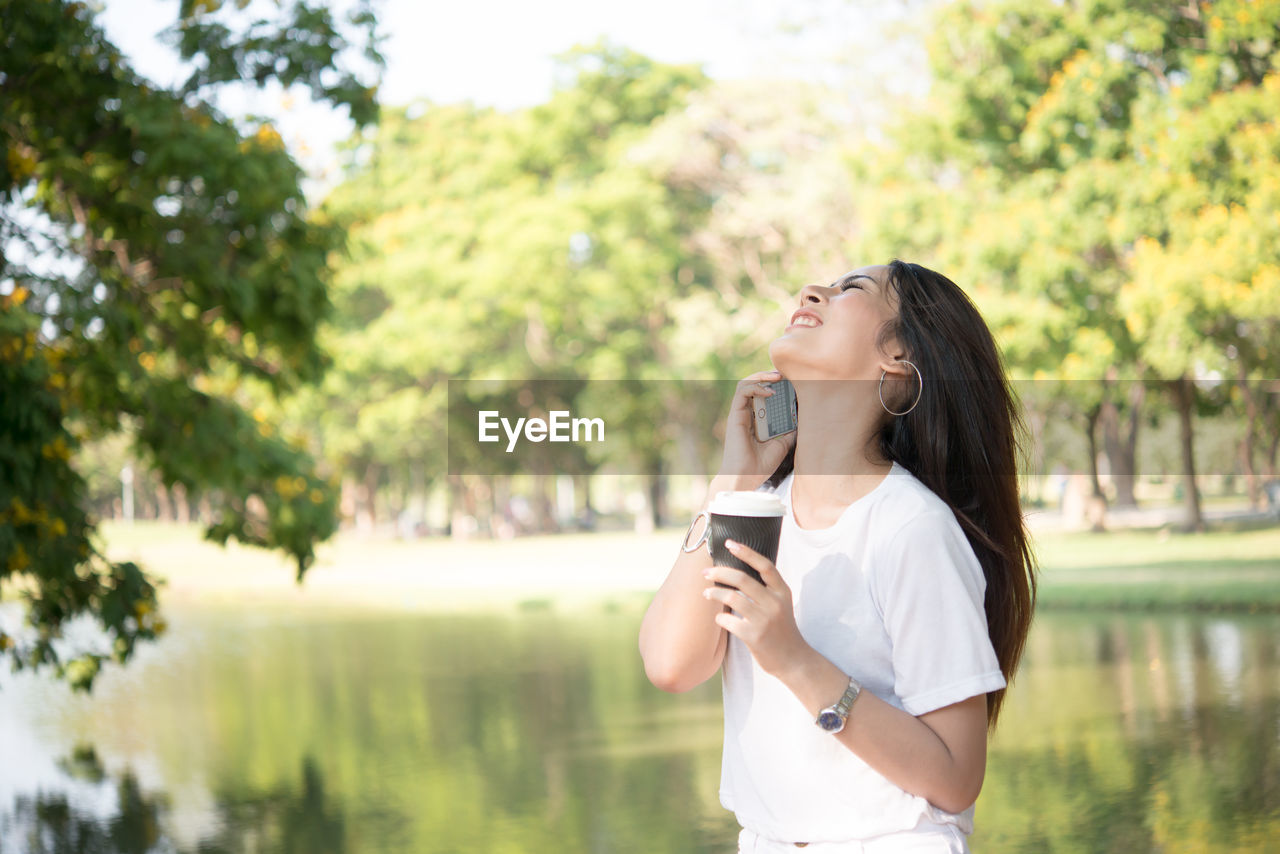 Smiling woman talking on mobile phone while holding disposable cup by lake