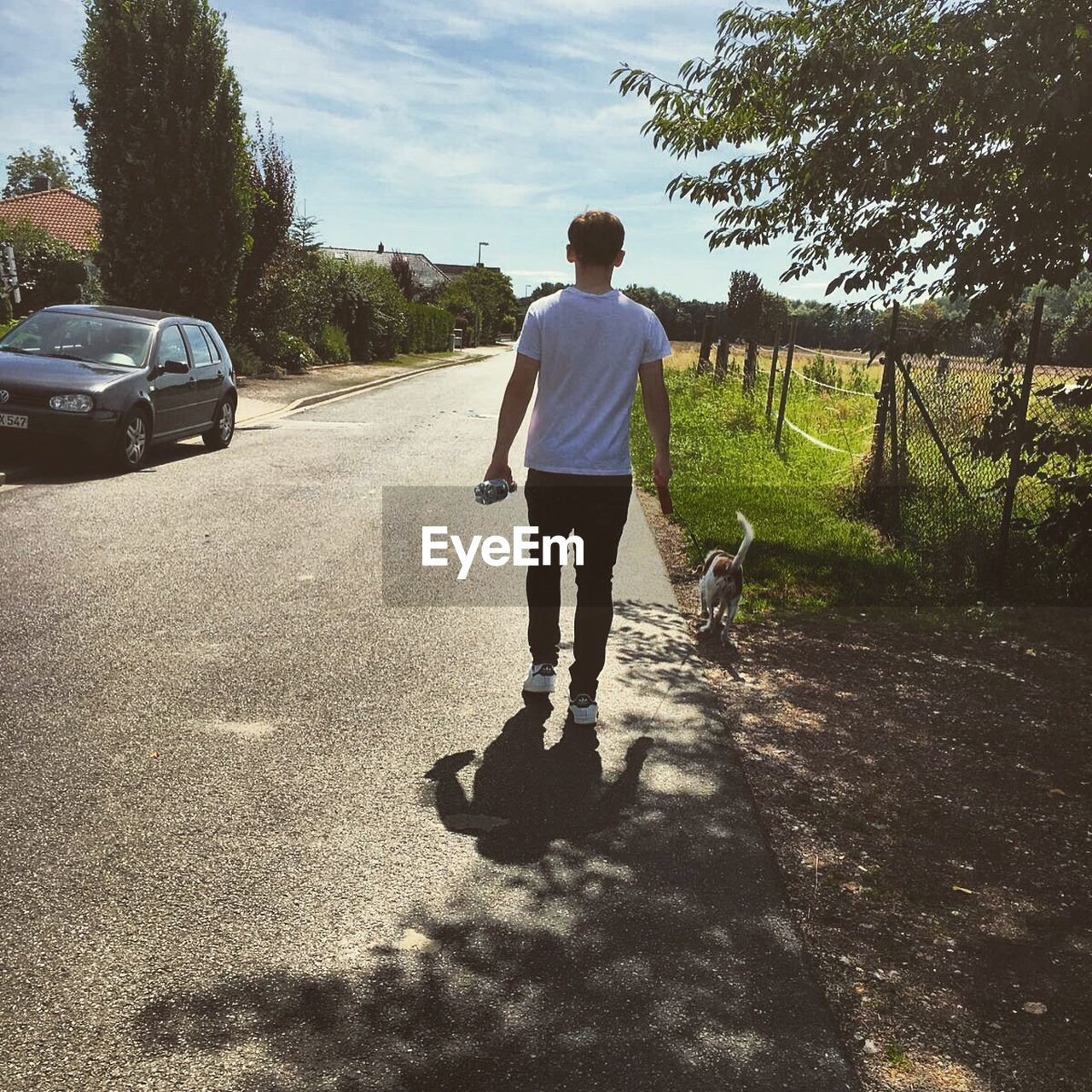 rear view, full length, real people, car, walking, sunlight, one person, shadow, casual clothing, day, standing, tree, lifestyles, leisure activity, outdoors, road, men, nature, sky, people