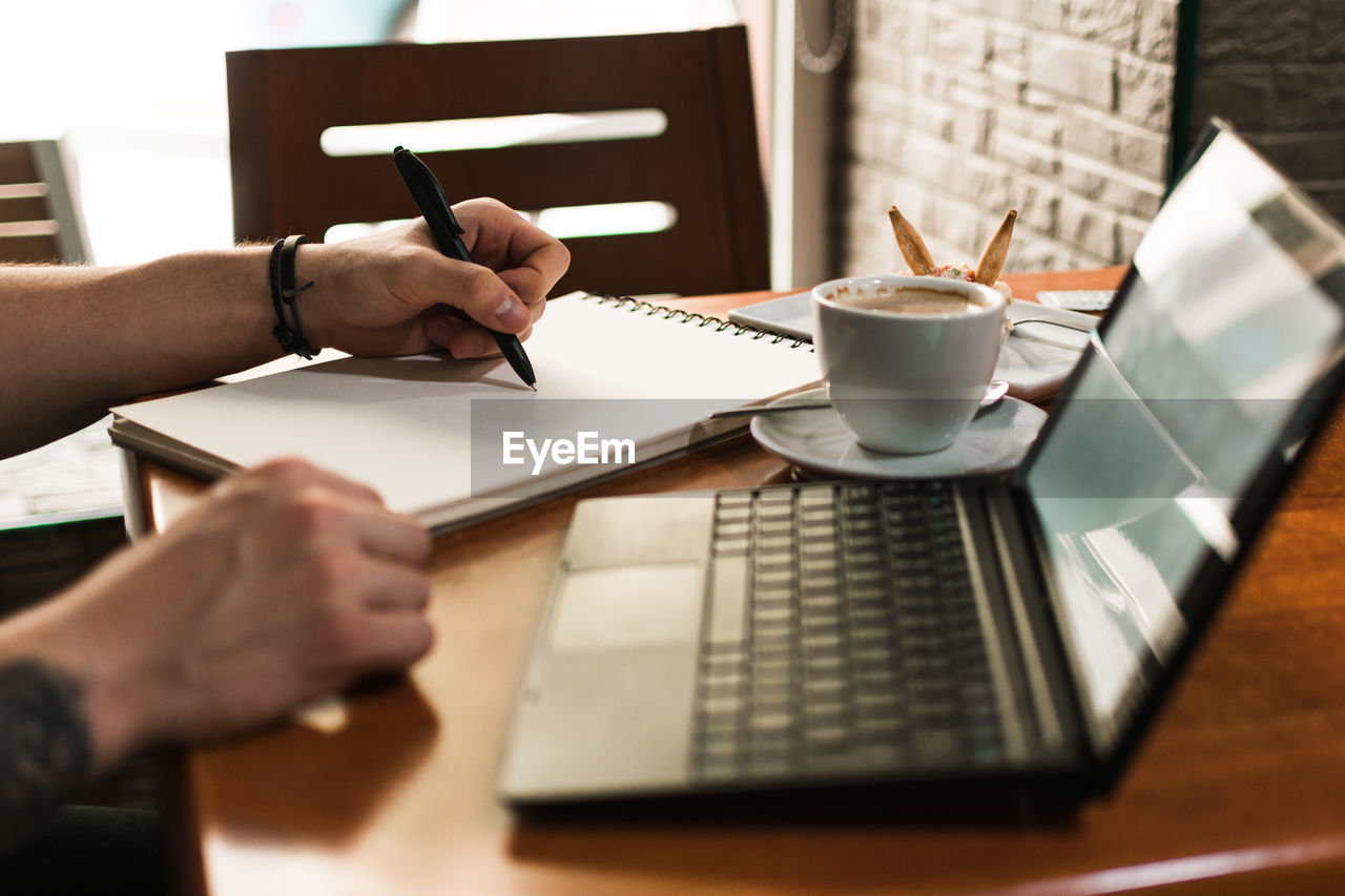 MIDSECTION OF COFFEE CUP ON TABLE WITH TEXT