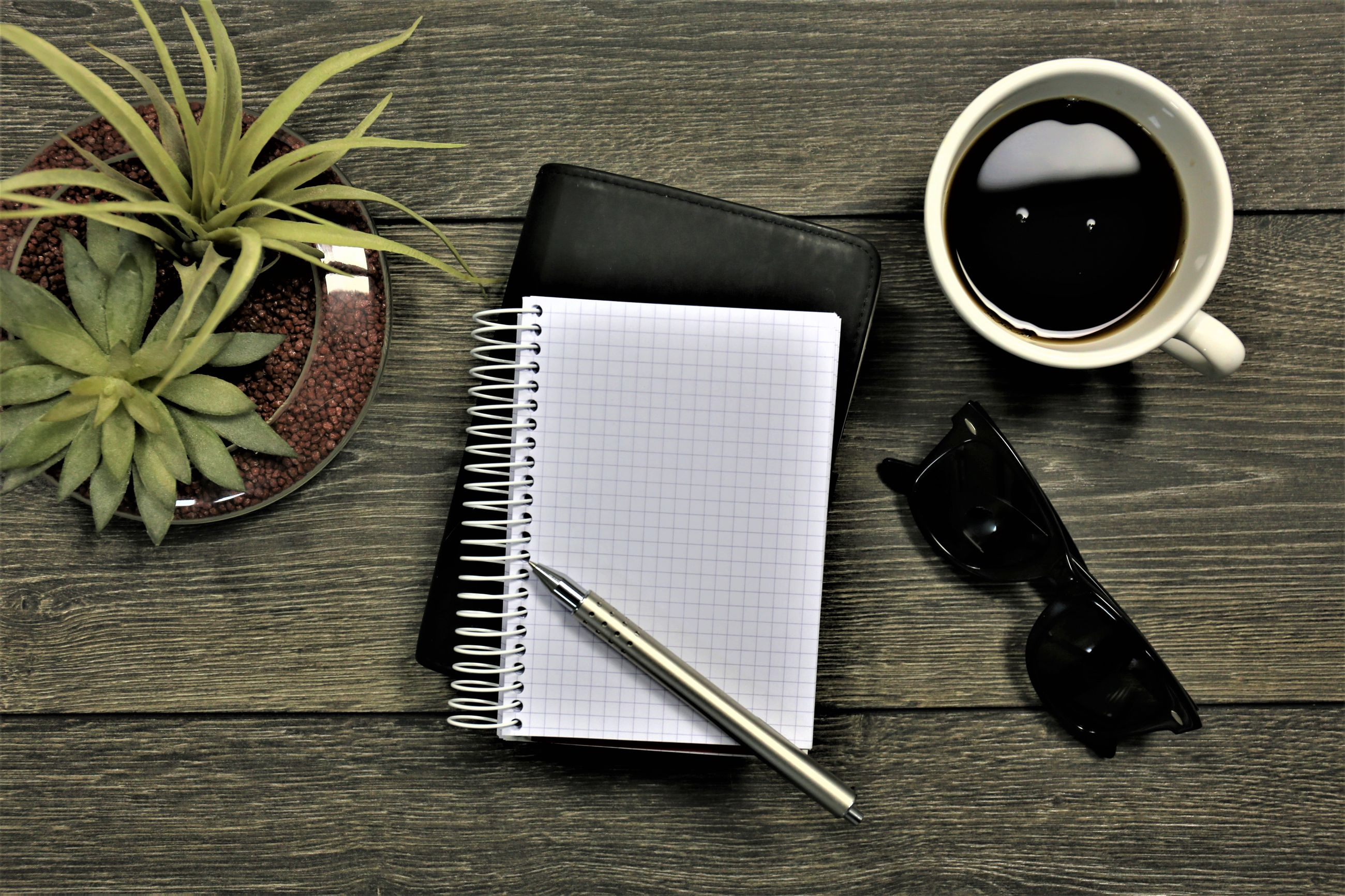 Directly above shot of coffee by note pad and sunglasses on table