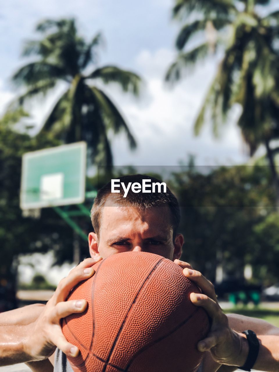 Close-up portrait of a man holding basketball