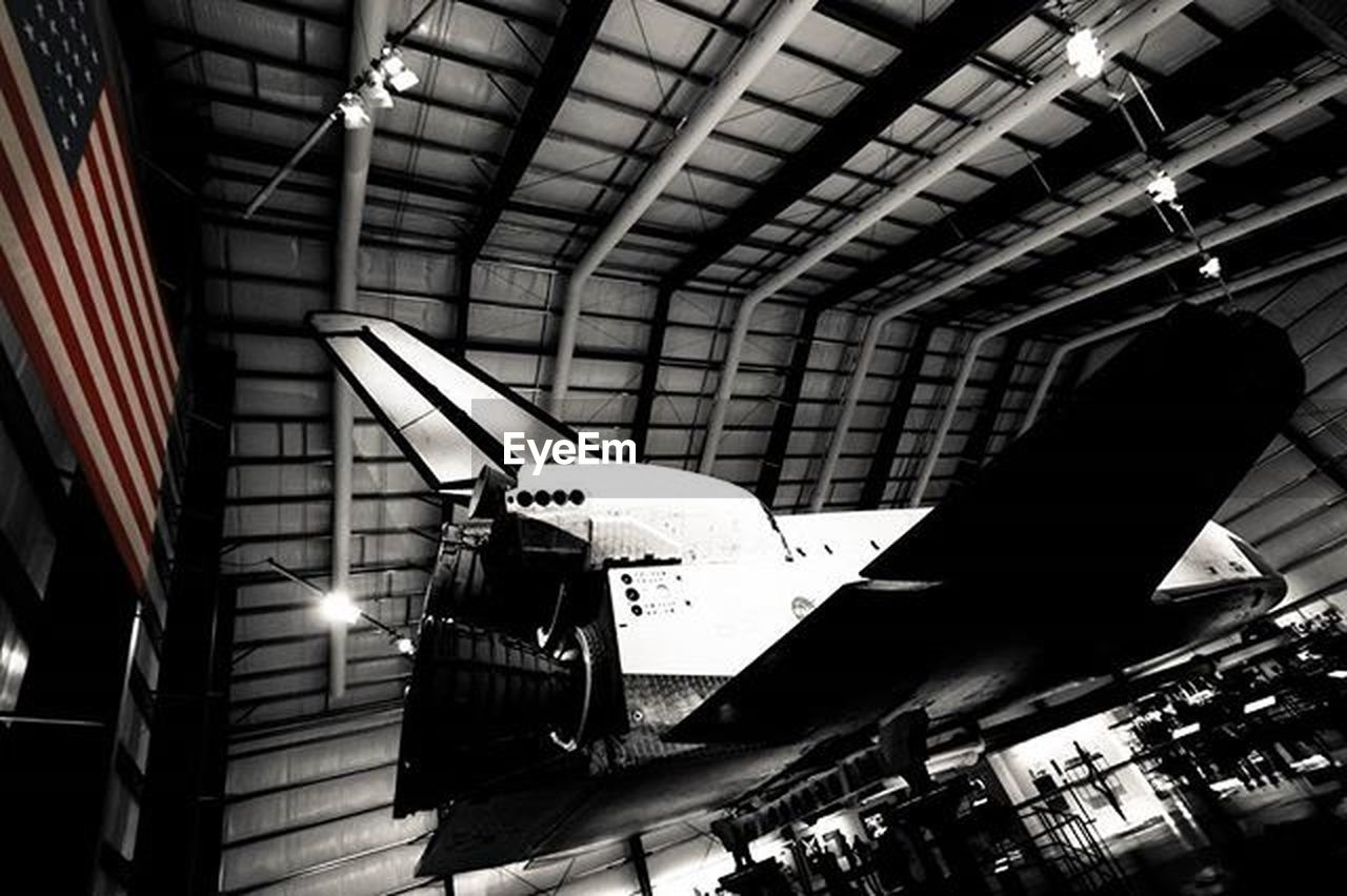 airplane, air vehicle, ceiling, transportation, indoors, built structure, mode of transport, airplane hangar, no people, aerospace industry, low angle view, architecture, illuminated, commercial airplane, flying, fighter plane, day