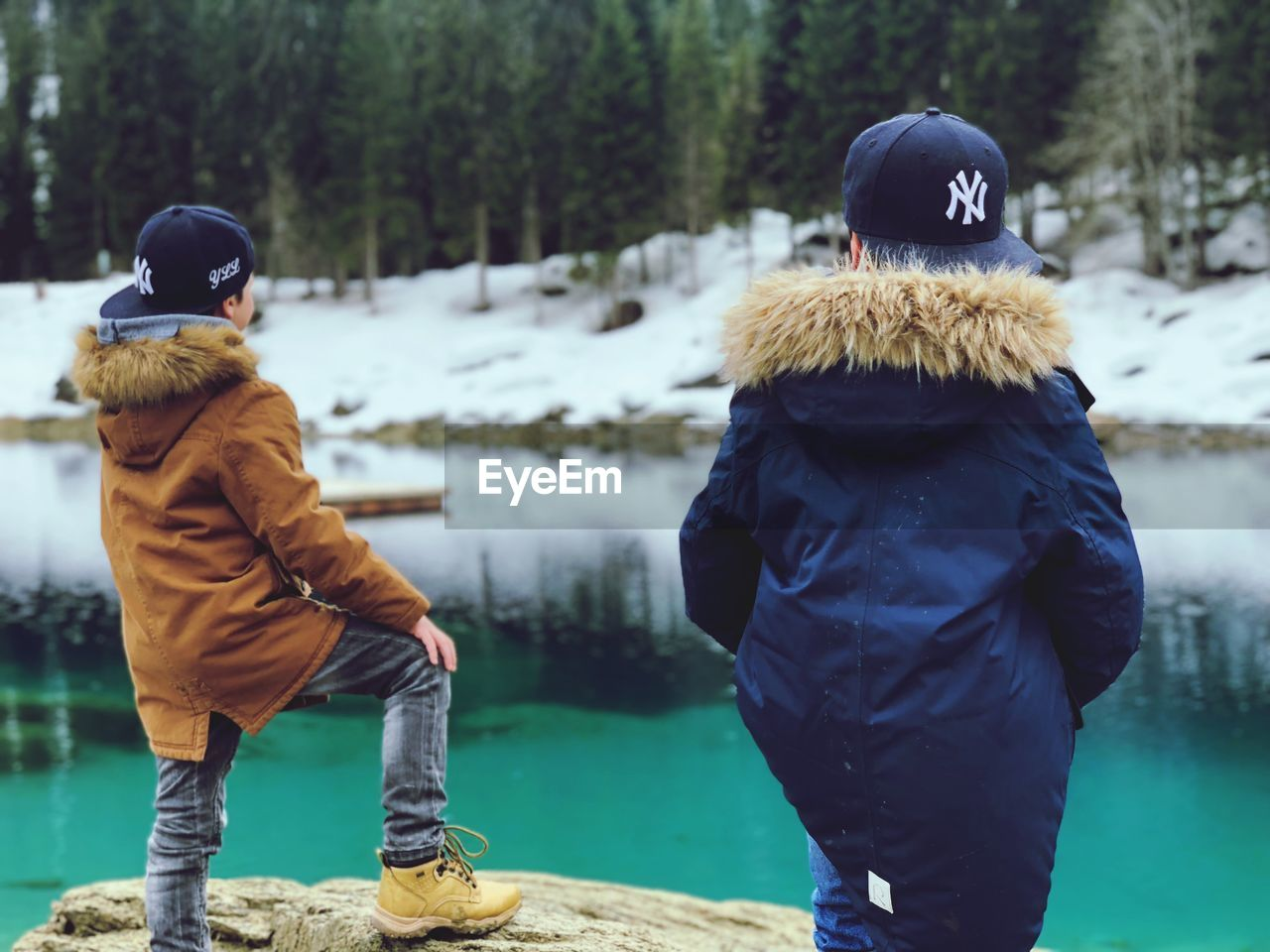 winter, cold temperature, warm clothing, clothing, real people, rear view, day, men, lifestyles, snow, two people, leisure activity, full length, tree, focus on foreground, nature, people, hat, plant, hood - clothing, outdoors