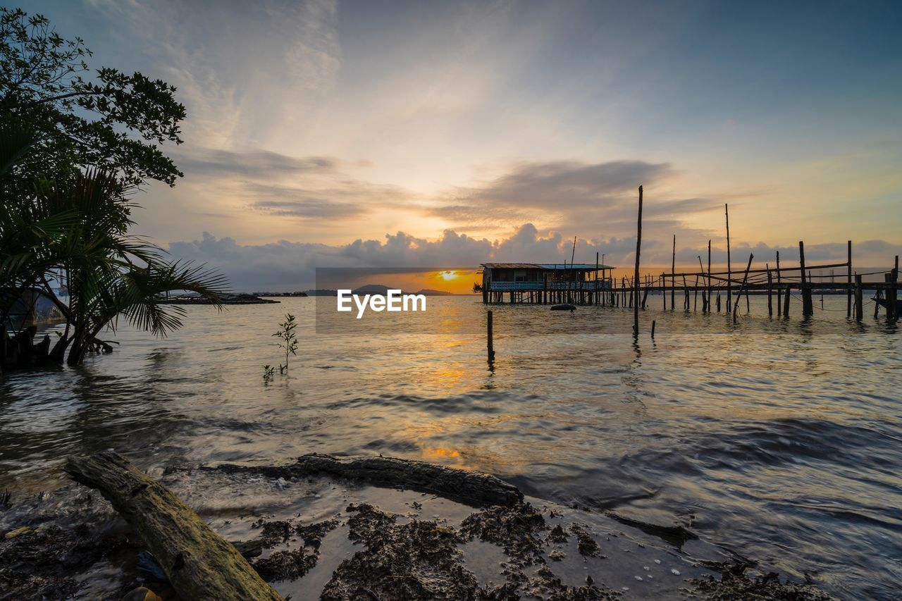 water, sky, sunset, cloud - sky, sea, scenics - nature, beauty in nature, beach, nature, tranquil scene, tranquility, no people, orange color, land, idyllic, non-urban scene, outdoors, architecture, built structure, wooden post