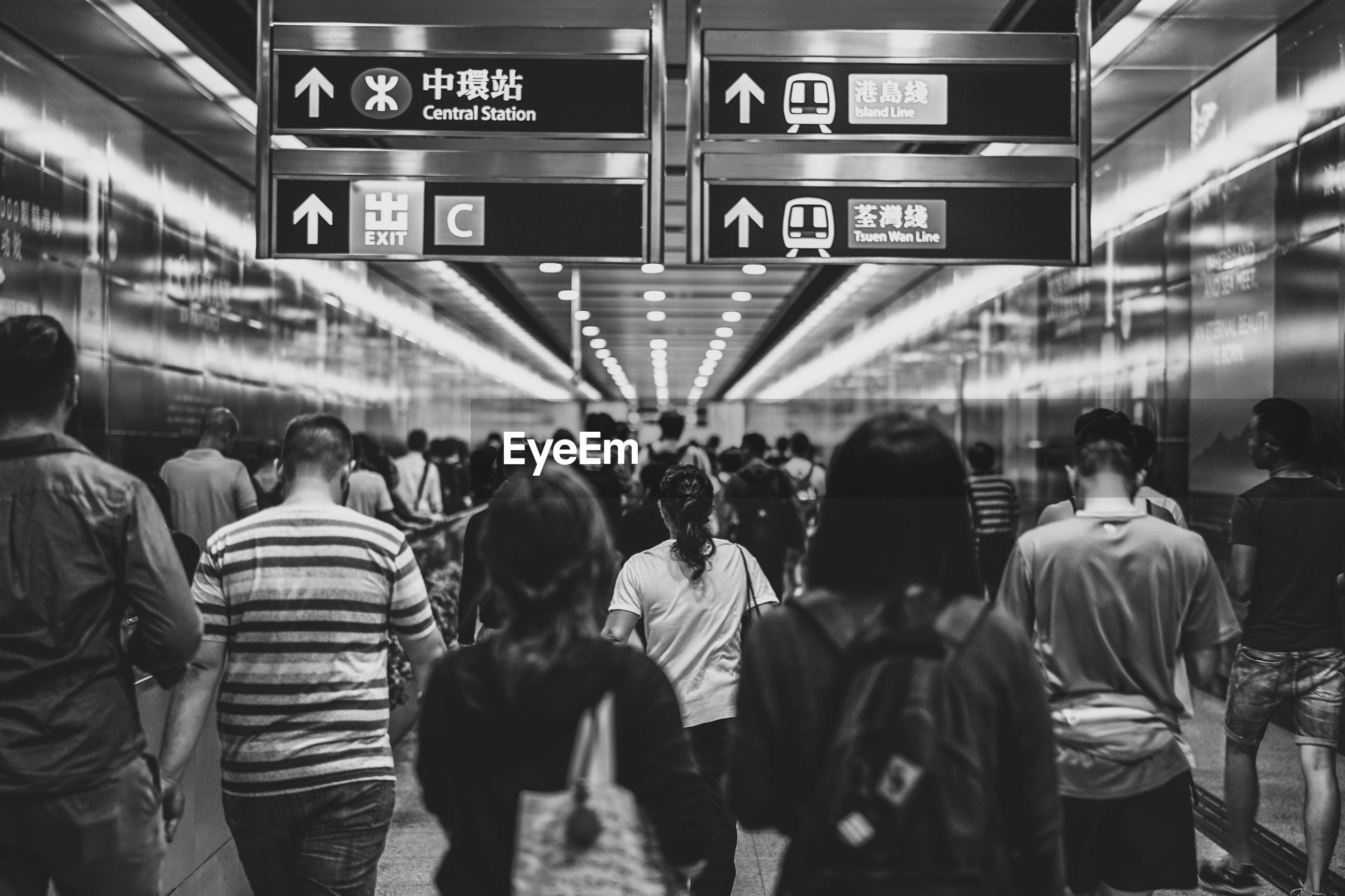 Rear view of people walking at subway station