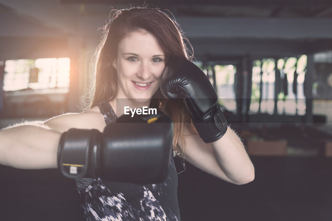 one person, young adult, young women, front view, looking at camera, focus on foreground, portrait, lifestyles, real people, boxing glove, adult, women, waist up, indoors, hairstyle, long hair, boxing - sport, beautiful woman