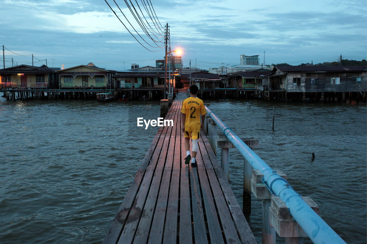View Of Boy On Pier Against Sky