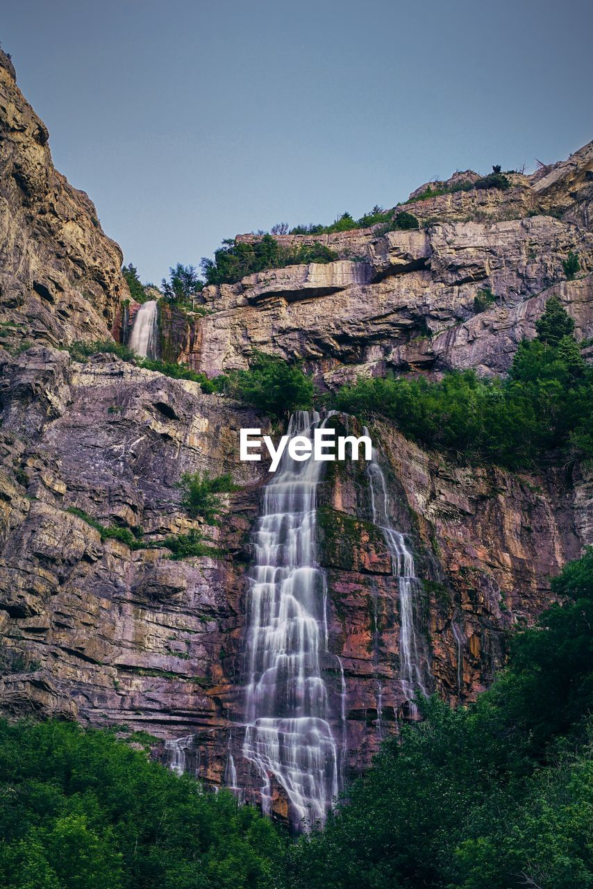 Scenic View Of Waterfall Against Clear Sky In Forest