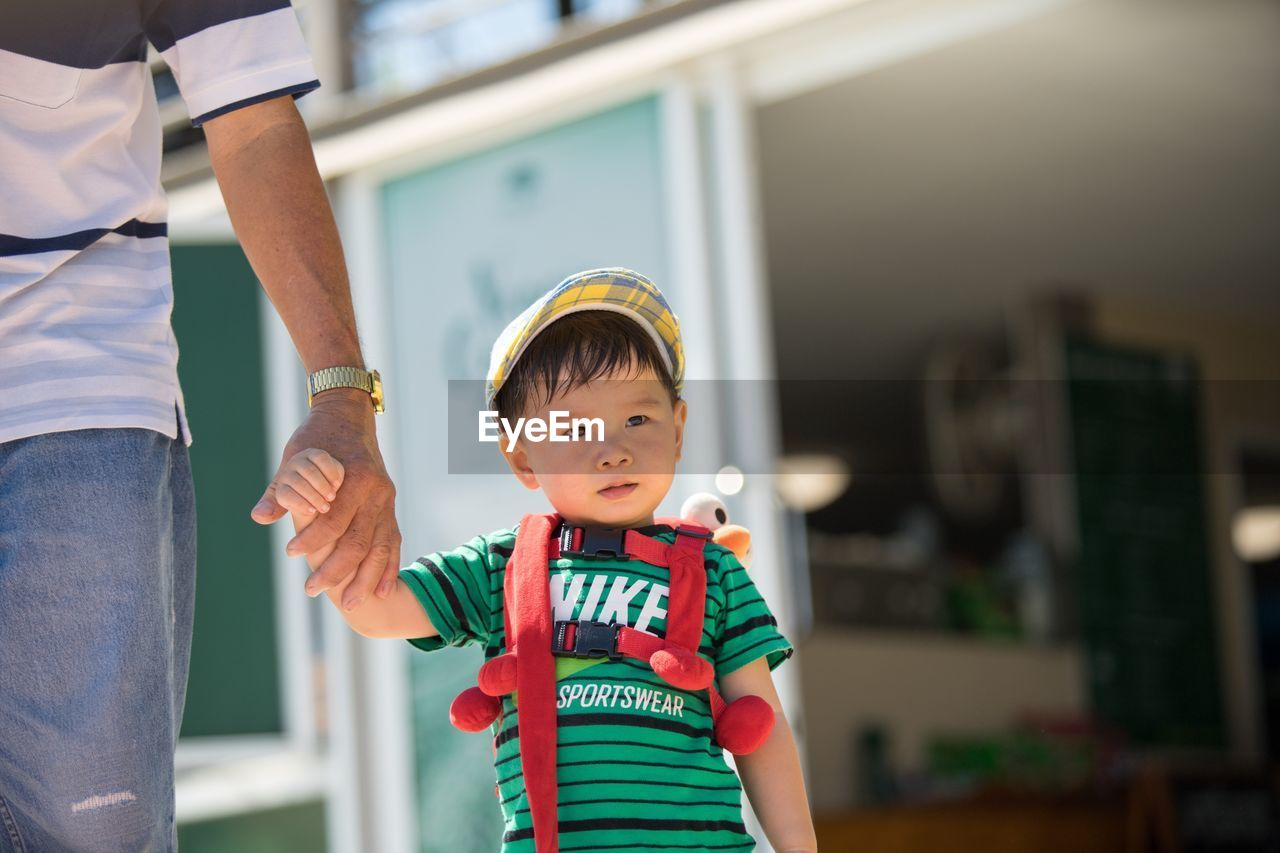 Midsection of father holding cute son hand while standing outdoors