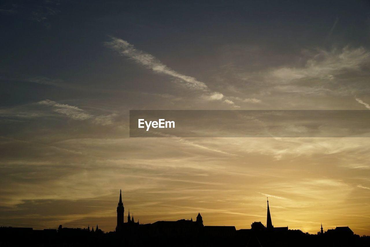 Silhouette buildings against sunset sky