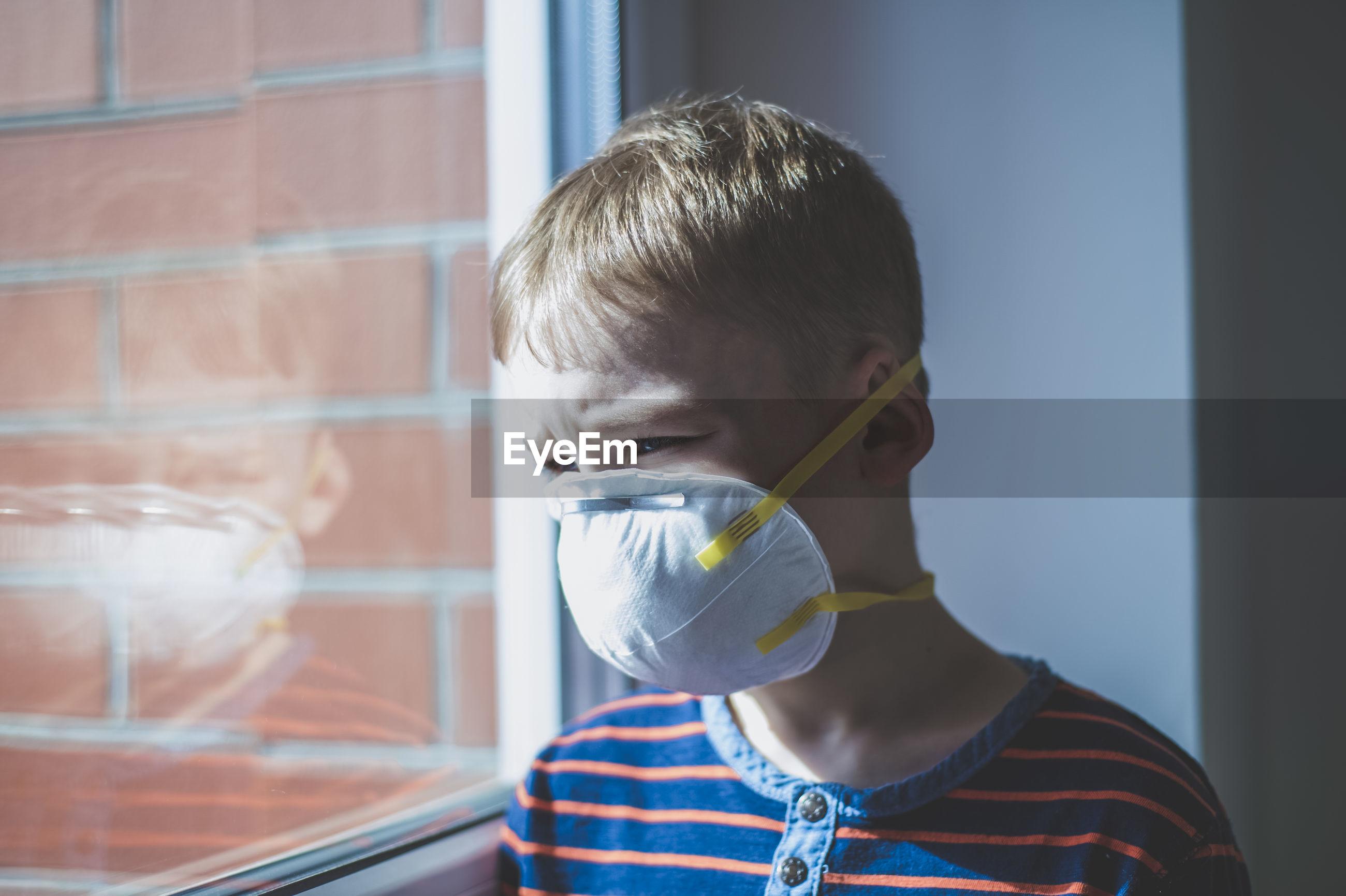 Portrait of boy drinking from window