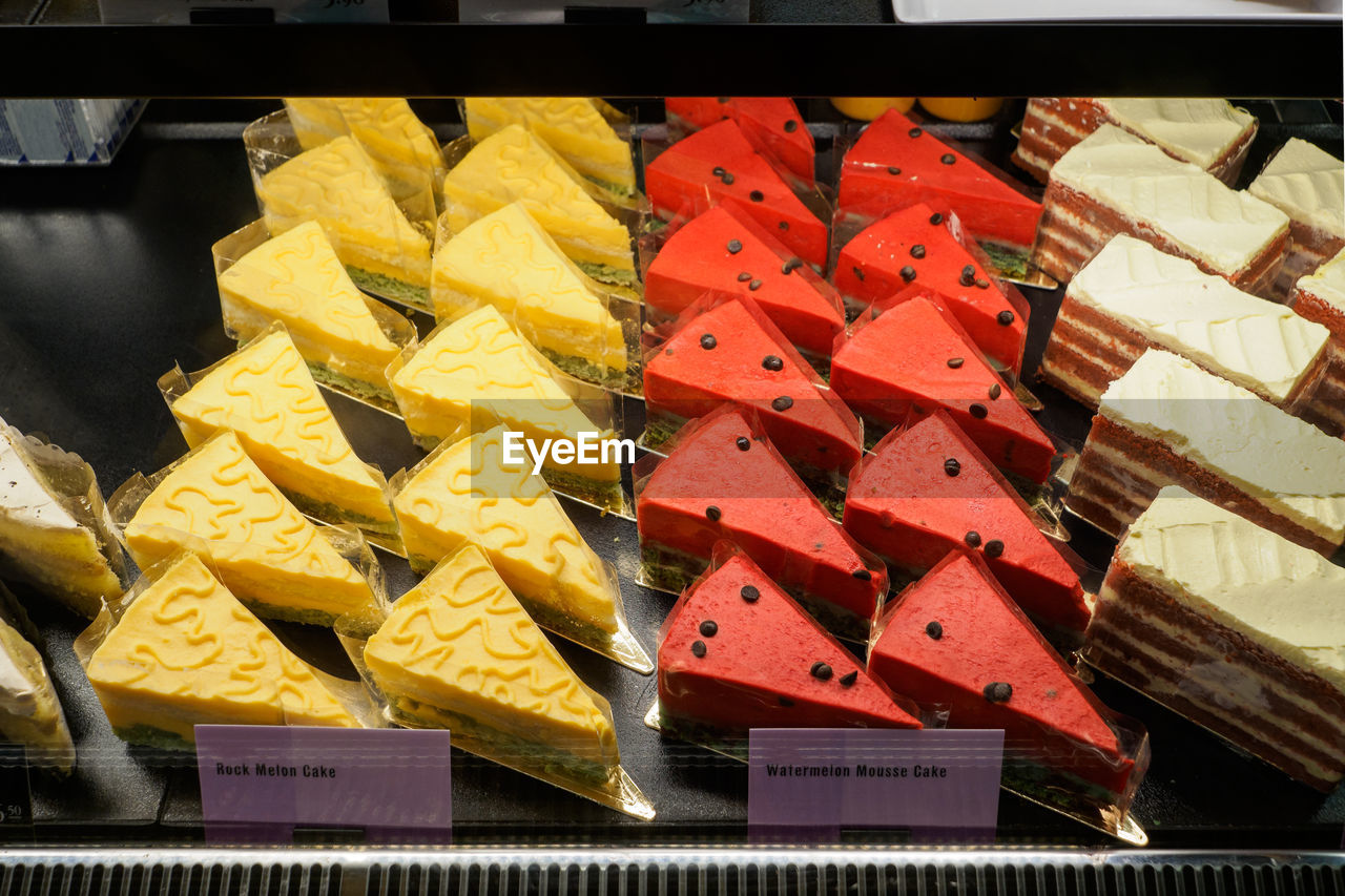 food, large group of objects, food and drink, multi colored, choice, variation, still life, no people, indoors, freshness, abundance, yellow, healthy eating, retail, for sale, close-up, high angle view, fruit, sweet food, slice, sale, retail display, tray, temptation