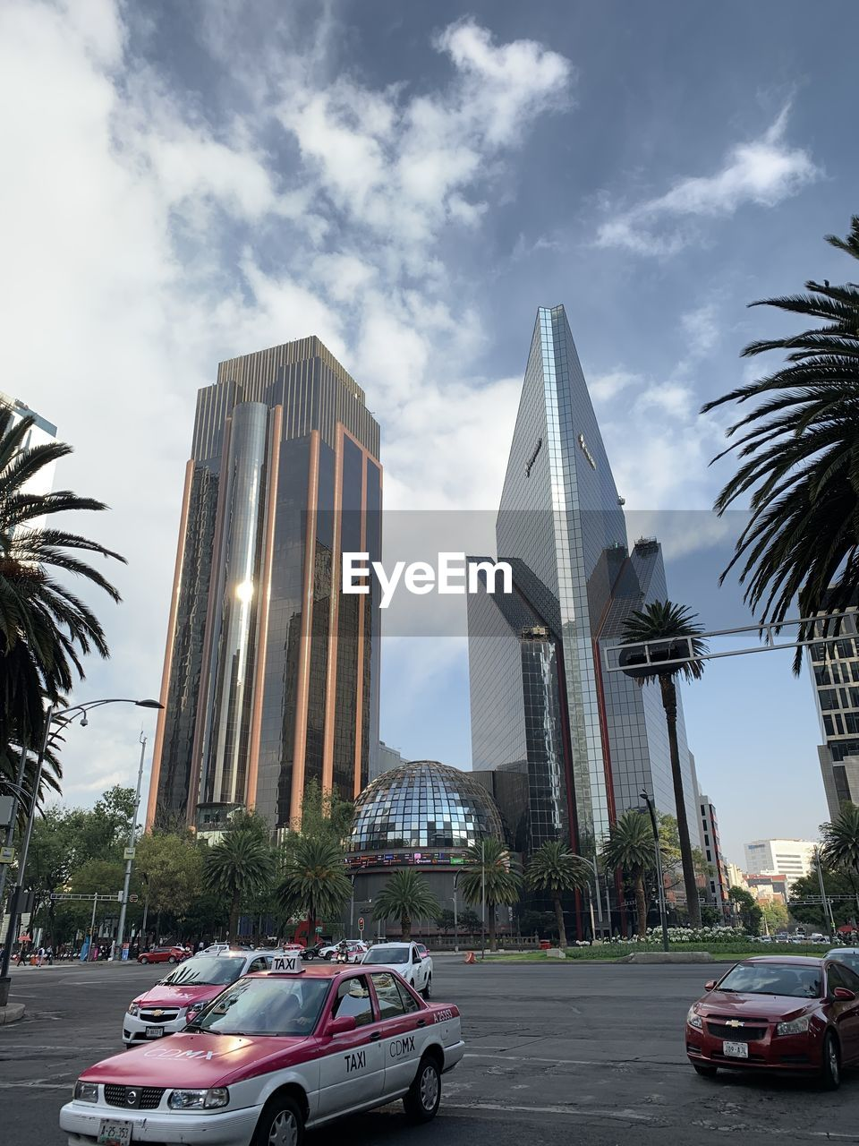 sky, palm tree, architecture, transportation, car, motor vehicle, tropical climate, building exterior, built structure, mode of transportation, tree, city, cloud - sky, land vehicle, nature, plant, building, office building exterior, day, street, tall - high, no people, outdoors, skyscraper, modern, luxury
