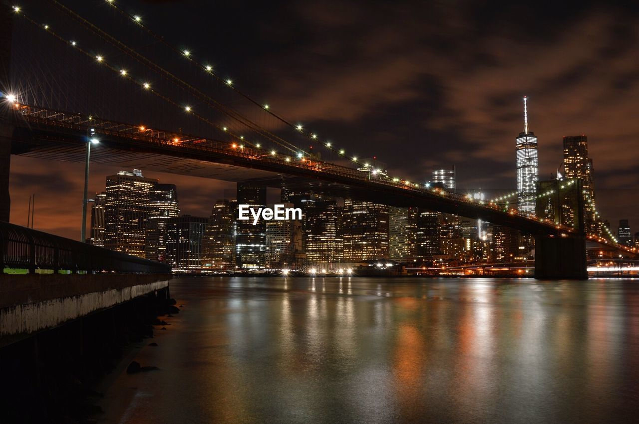 Low Angle View Of Illuminated Brooklyn Bridge Over River Against Sky At Night