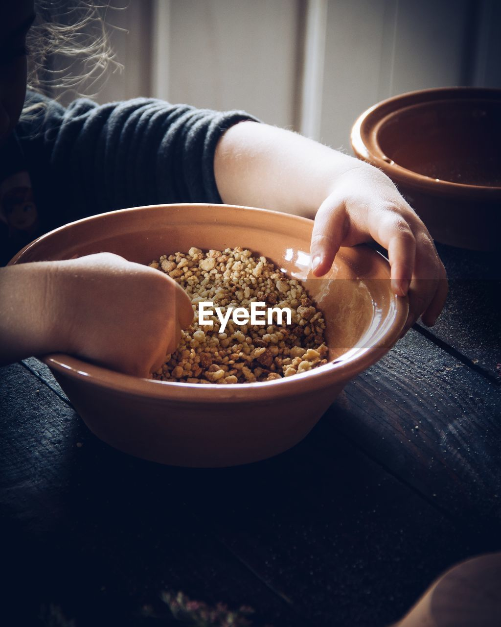 food and drink, one person, bowl, food, real people, human hand, freshness, human body part, hand, lifestyles, holding, table, indoors, women, body part, healthy eating, unrecognizable person, wellbeing, midsection, finger, breakfast, snack