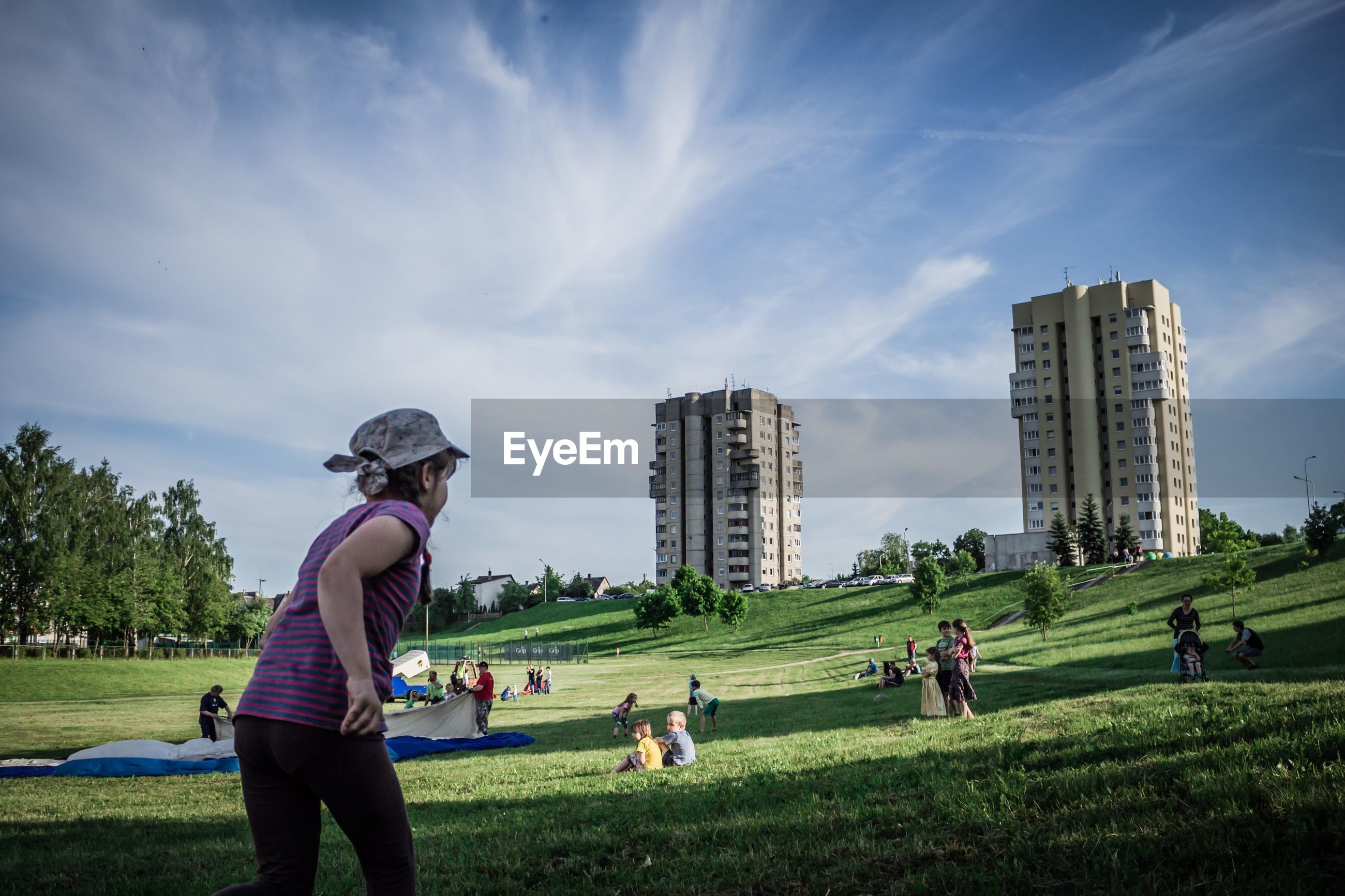 grass, real people, leisure activity, sky, cloud - sky, lifestyles, playing, day, field, green color, architecture, outdoors, men, casual clothing, golf, golf course, built structure, building exterior, growth, nature, togetherness, women, golf club, green - golf course, golfer, sportsman, people