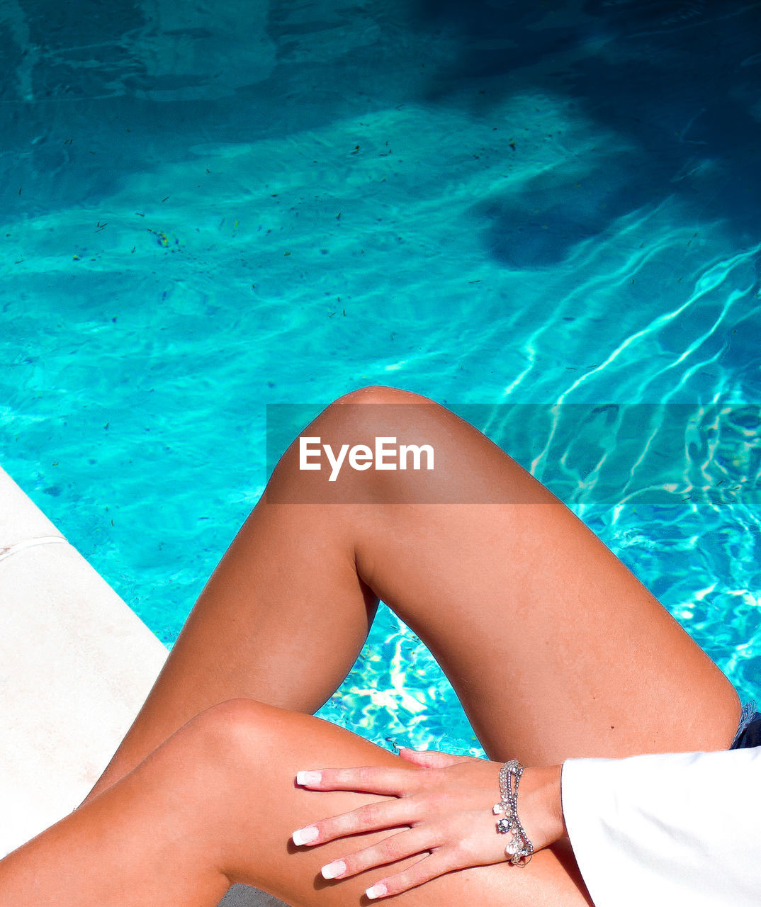 Midsection of woman by swimming pool
