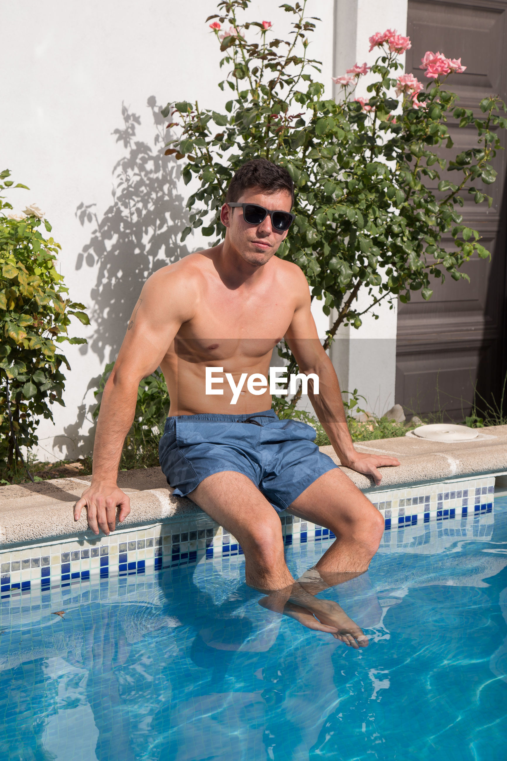 Portrait of handsome young shirtless man sitting at poolside