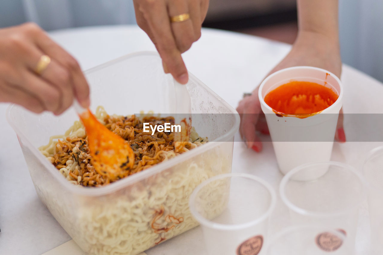 Cropped Hands Of Friends Preparing Korean Instant Noodles On Table