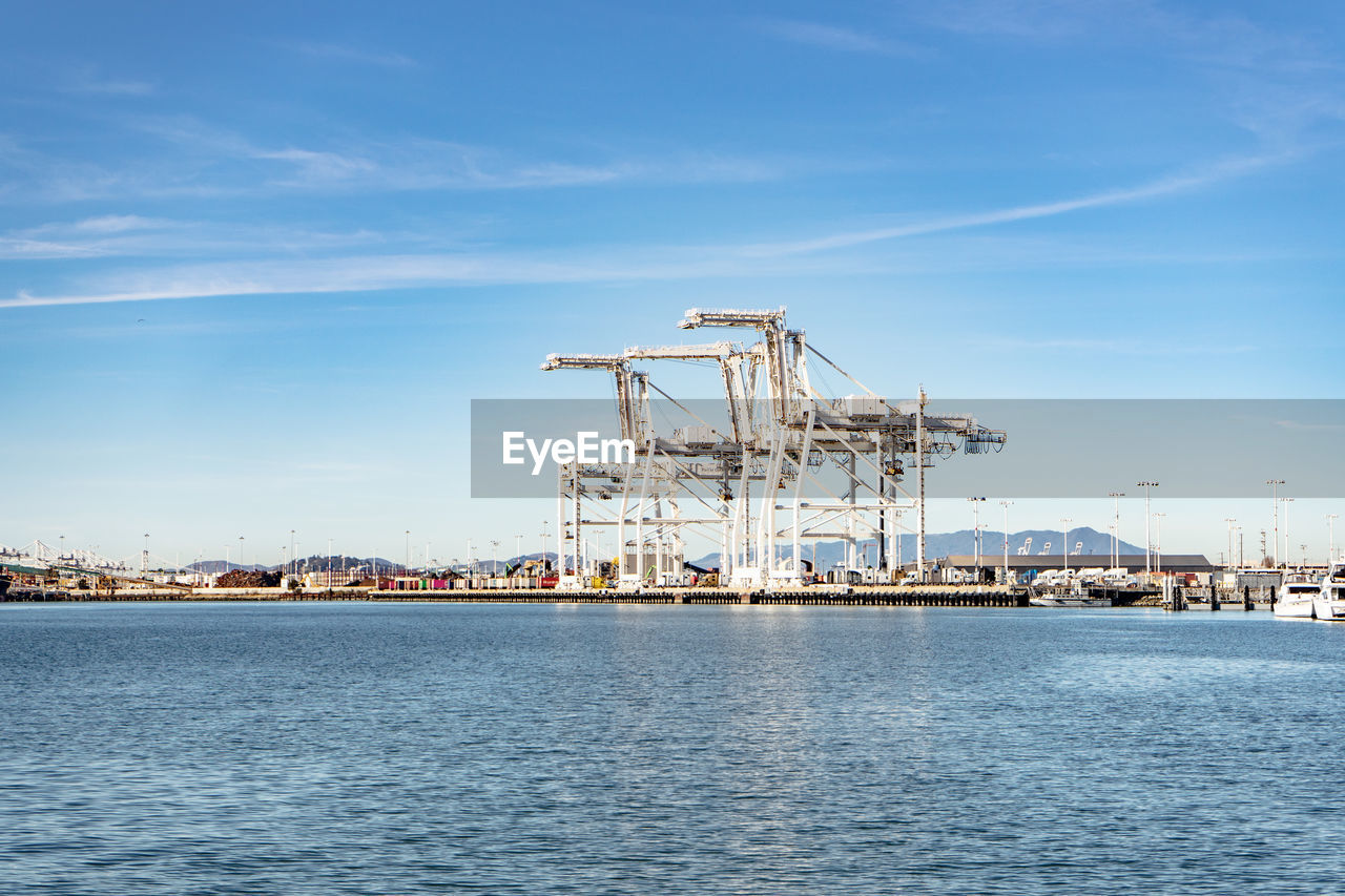 water, sky, industry, architecture, waterfront, nature, cloud - sky, crane - construction machinery, machinery, pier, no people, commercial dock, built structure, day, harbor, blue, transportation, sea, outdoors, construction equipment