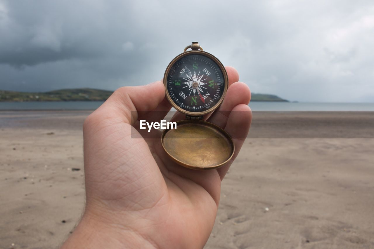 Close-up of hand compass at beach