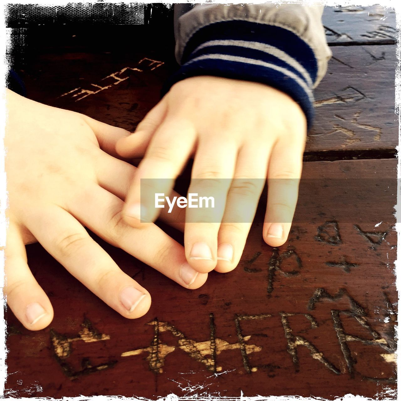 Close-up of child hands on table