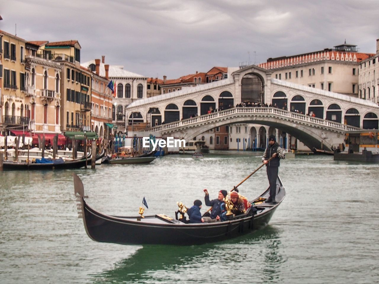 architecture, built structure, building exterior, men, transportation, real people, gondola - traditional boat, canal, gondolier, large group of people, nautical vessel, tourism, day, travel destinations, oar, water, women, outdoors, sky, rowing, city, adult, people