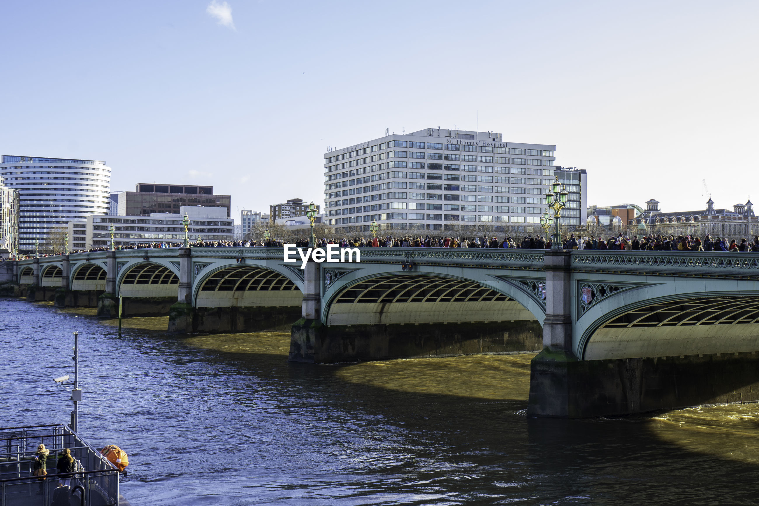 Westminster bridge over river thames in front of buildings against clear sky