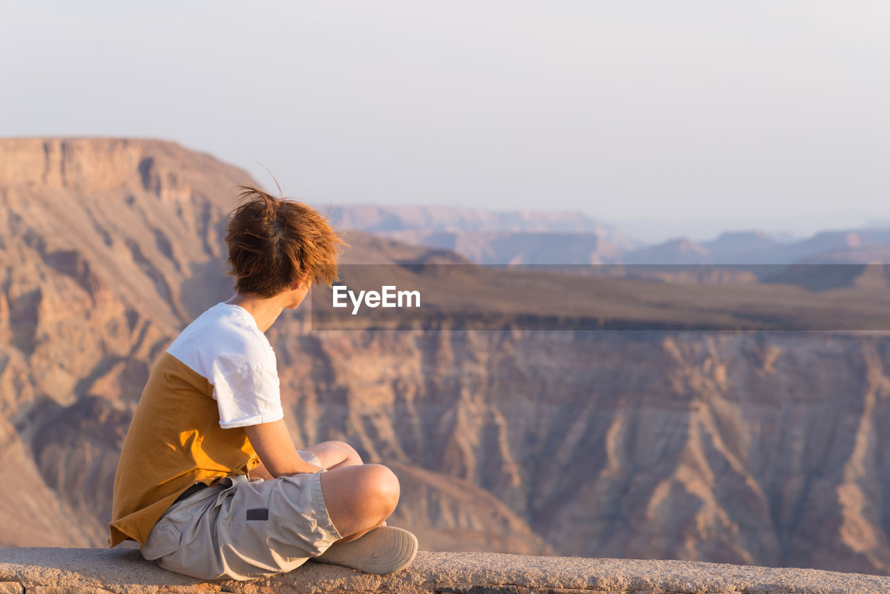 Woman sitting on mountain while looking at view
