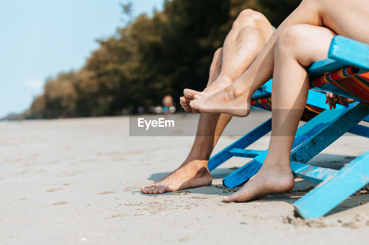 Low section of couple sitting on chairs at beach
