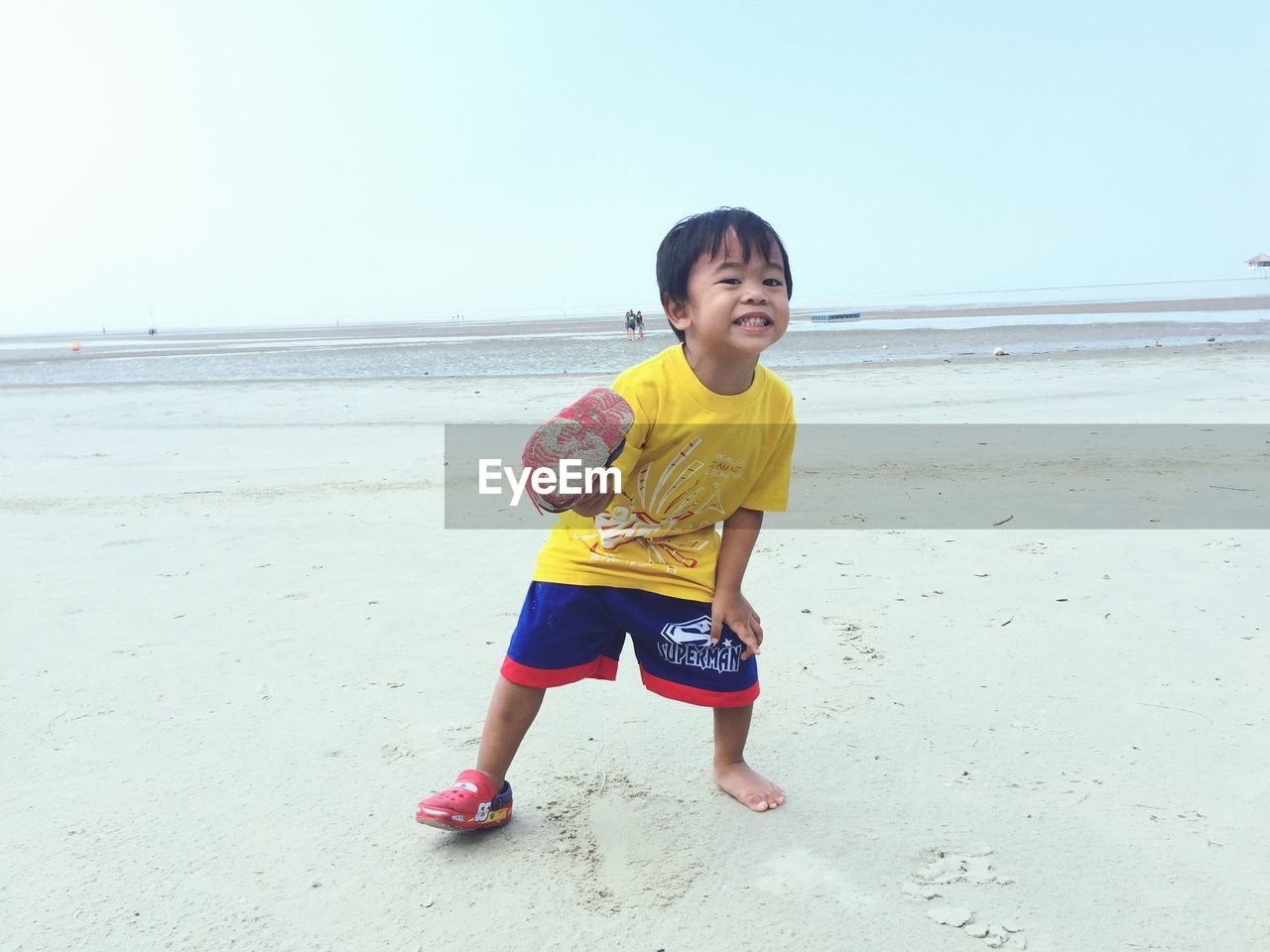 Full length of boy playing at beach against sky