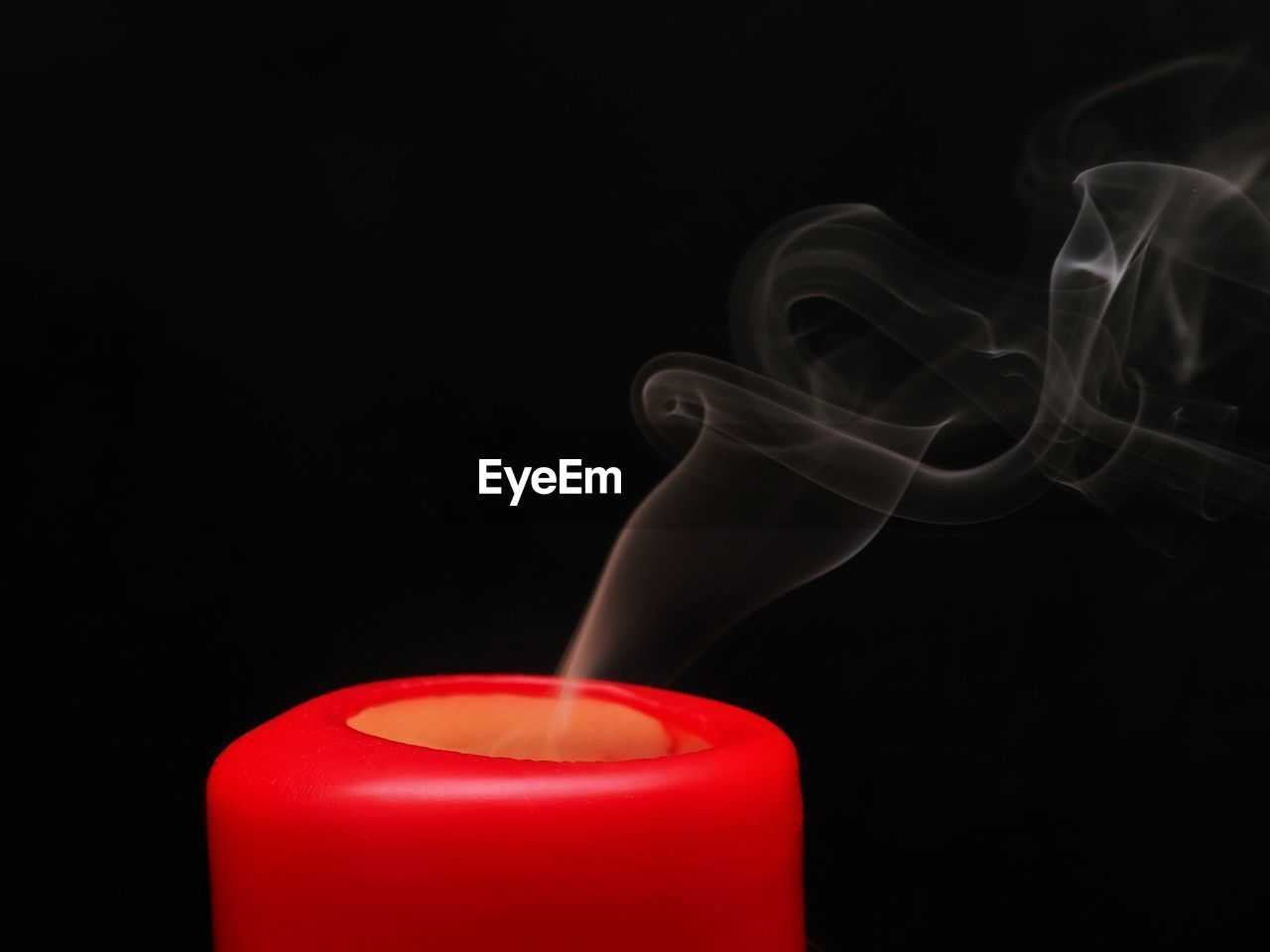 black background, studio shot, smoke - physical structure, red, candle, indoors, copy space, motion, burning, close-up, no people, fire, heat - temperature, flame, container, wax, extinguishing, fire - natural phenomenon, still life, scented, changing form