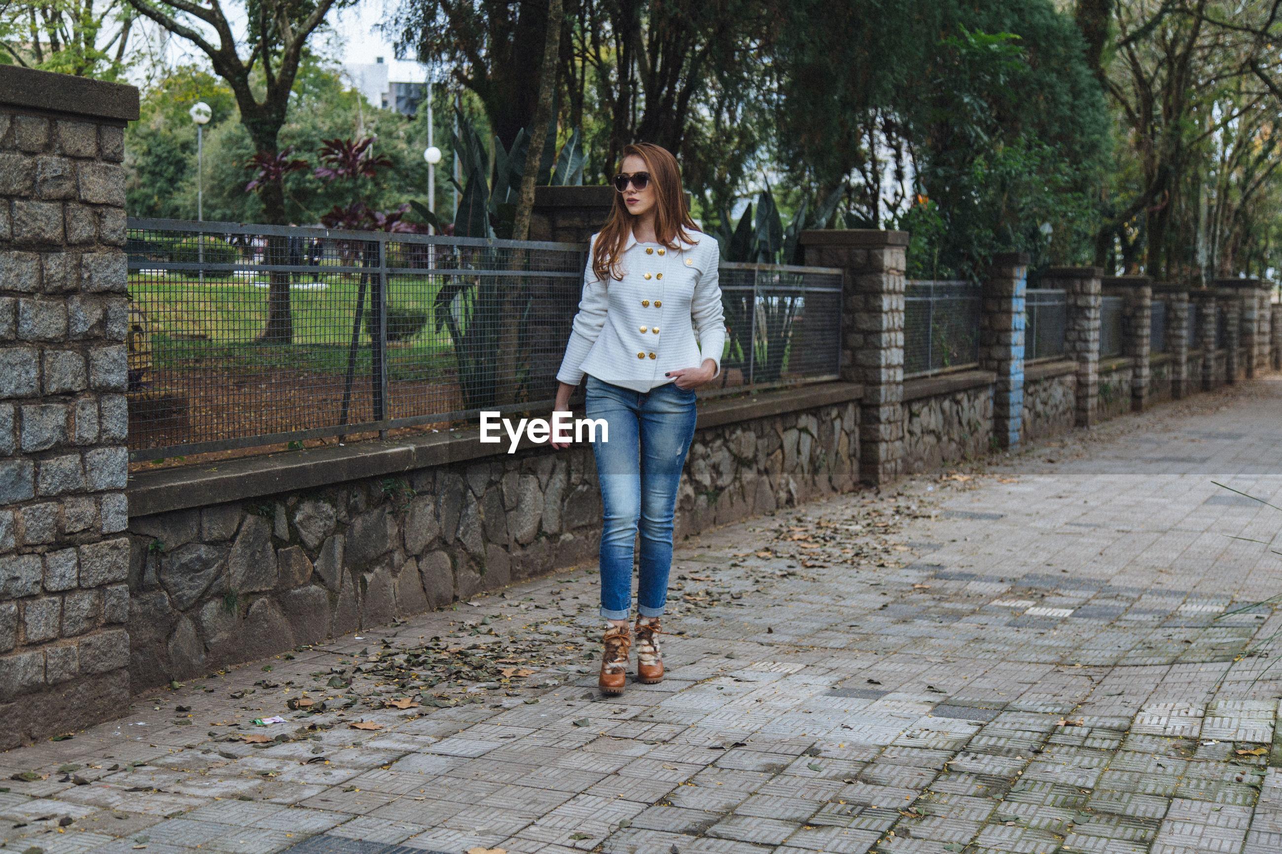 Woman in sunglasses walking on sidewalk